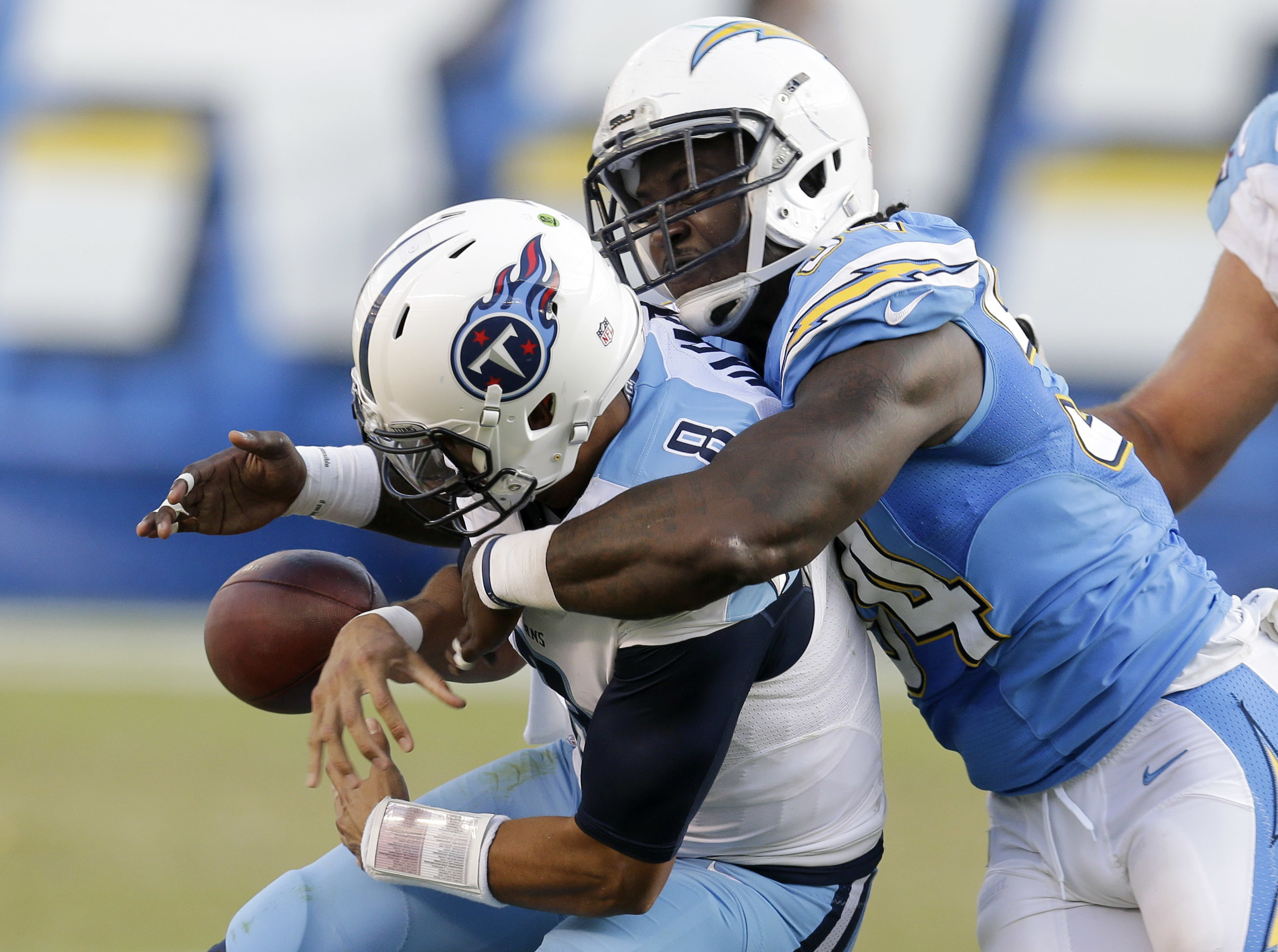FILe - In this Nov. 6, 2016, file photo, Tennessee Titans quarterback Marcus Mariota, left, fumbles the ball as he is brought down by San Diego Chargers outside linebacker Melvin Ingram during the second half of an NFL football game, in San Diego. The Cha