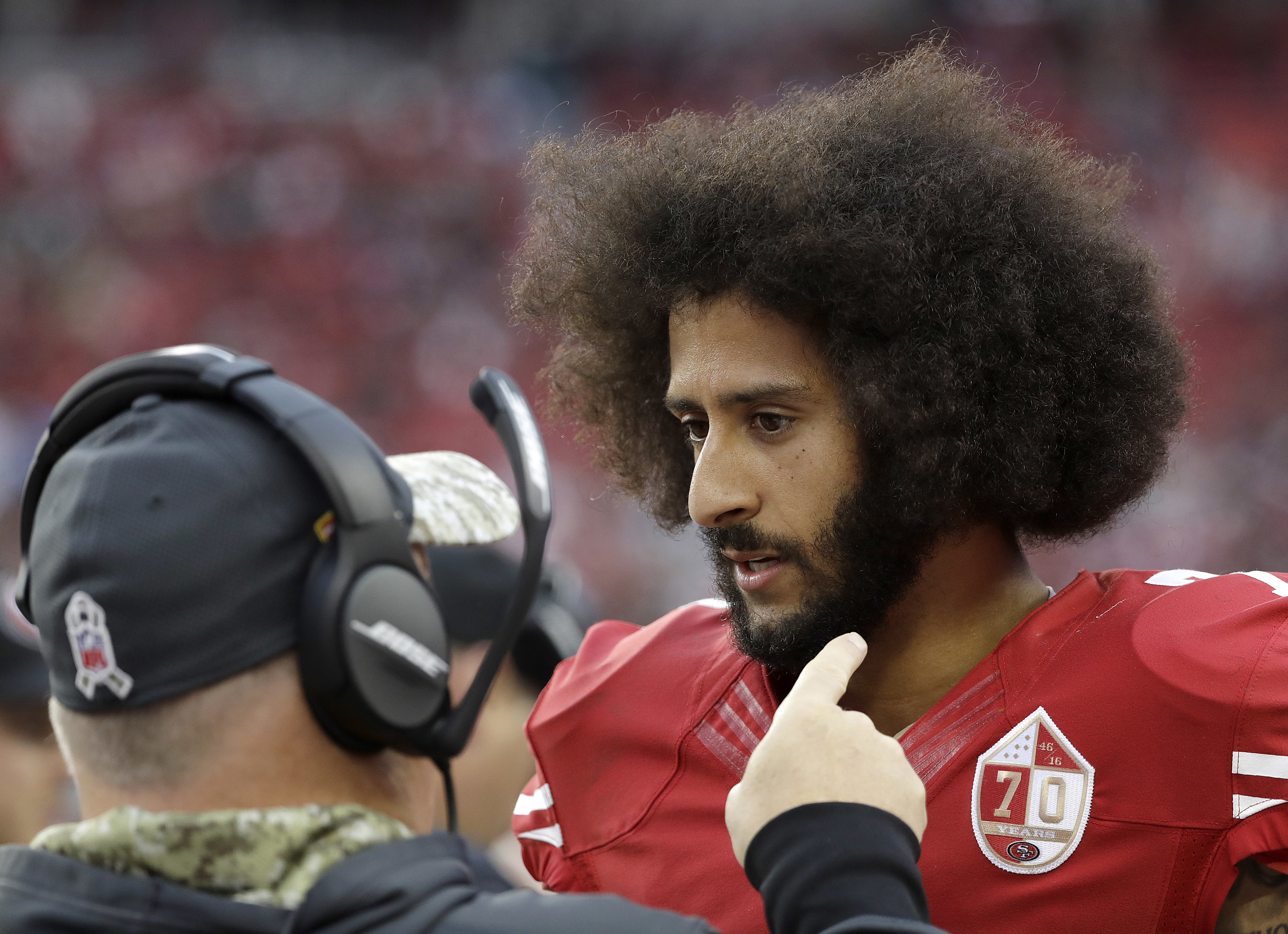 FILE - In this Dec. 11, 2016, file photo, San Francisco 49ers head coach Chip Kelly, left, talks with quarterback Colin Kaepernick during the second half of an NFL football game against the New York Jets, in Santa Clara, Calif. The 49ers are far from the