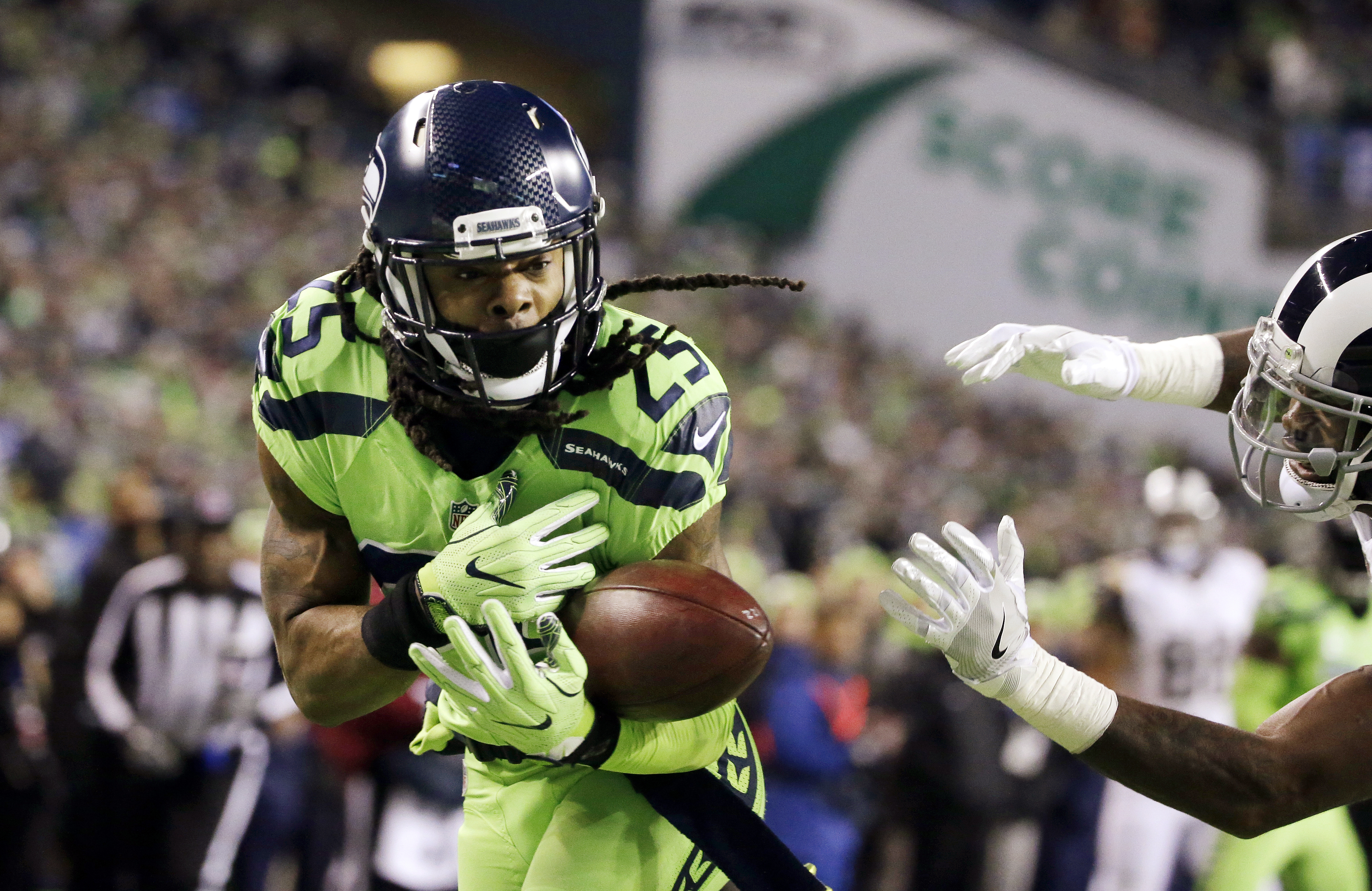 Seattle Seahawks cornerback Richard Sherman, left, bobbles a pass intended for Los Angeles Rams wide receiver Kenny Britt, right, in the first half of an NFL football game, Thursday, Dec. 15, 2016, in Seattle. (AP Photo/Elaine Thompson)