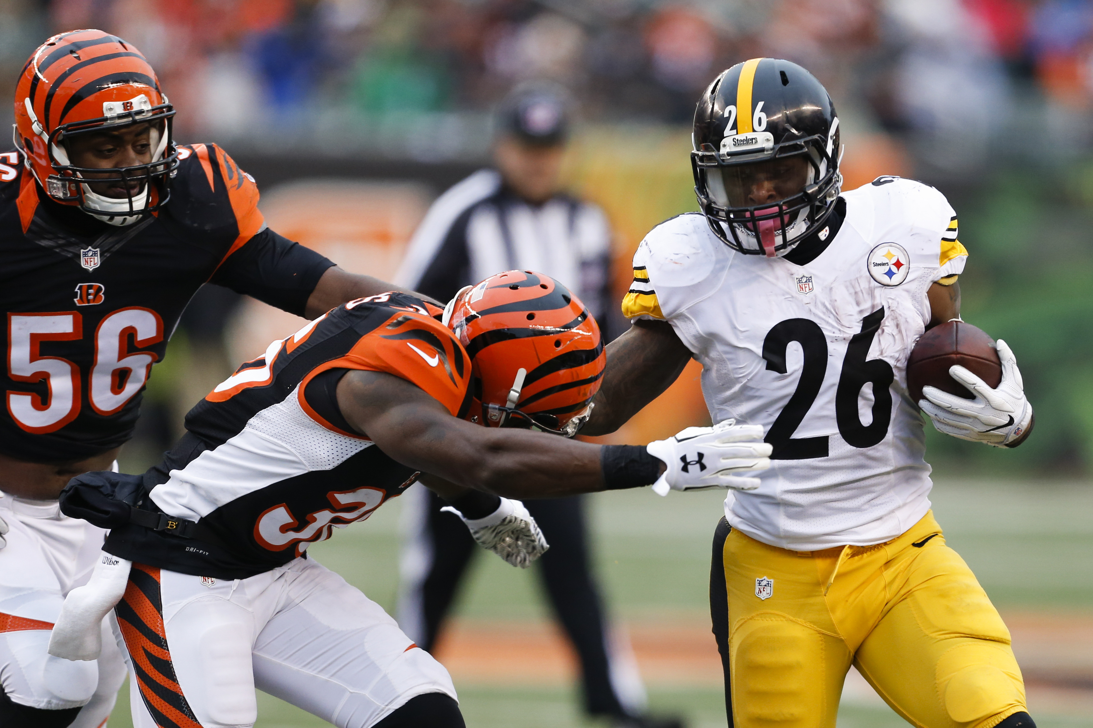 Pittsburgh Steelers running back Le'Veon Bell (26) runs the ball against Cincinnati Bengals strong safety Shawn Williams (36) in the second half of an NFL football game, Sunday, Dec. 18, 2016, in Cincinnati. (AP Photo/Gary Landers)