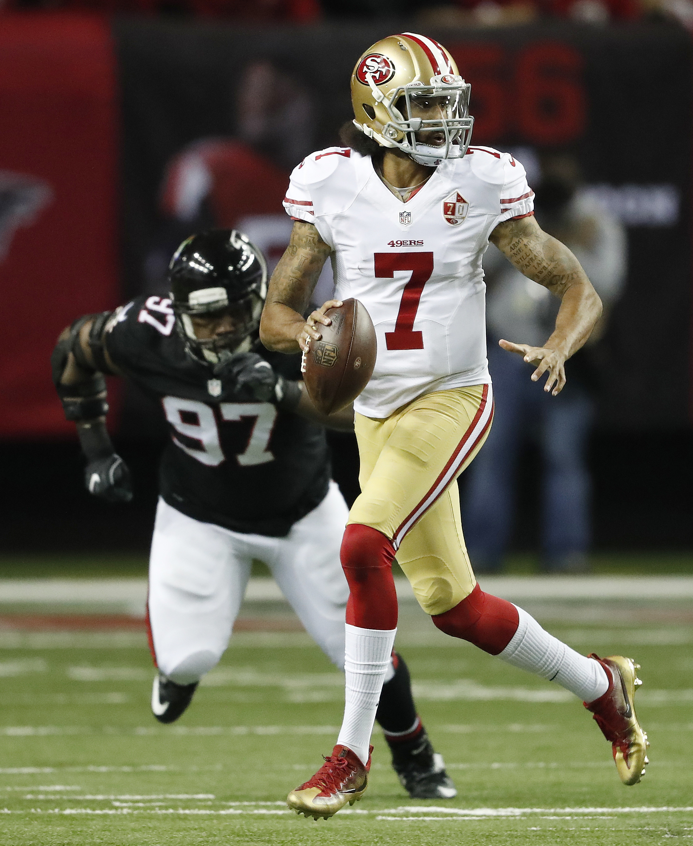 San Francisco 49ers quarterback Colin Kaepernick (7) runs out of the pocket as Atlanta Falcons defensive tackle Grady Jarrett (97) looks on during the first half of an NFL football game, Sunday, Dec. 18, 2016, in Atlanta. (AP Photo/John Bazemore)