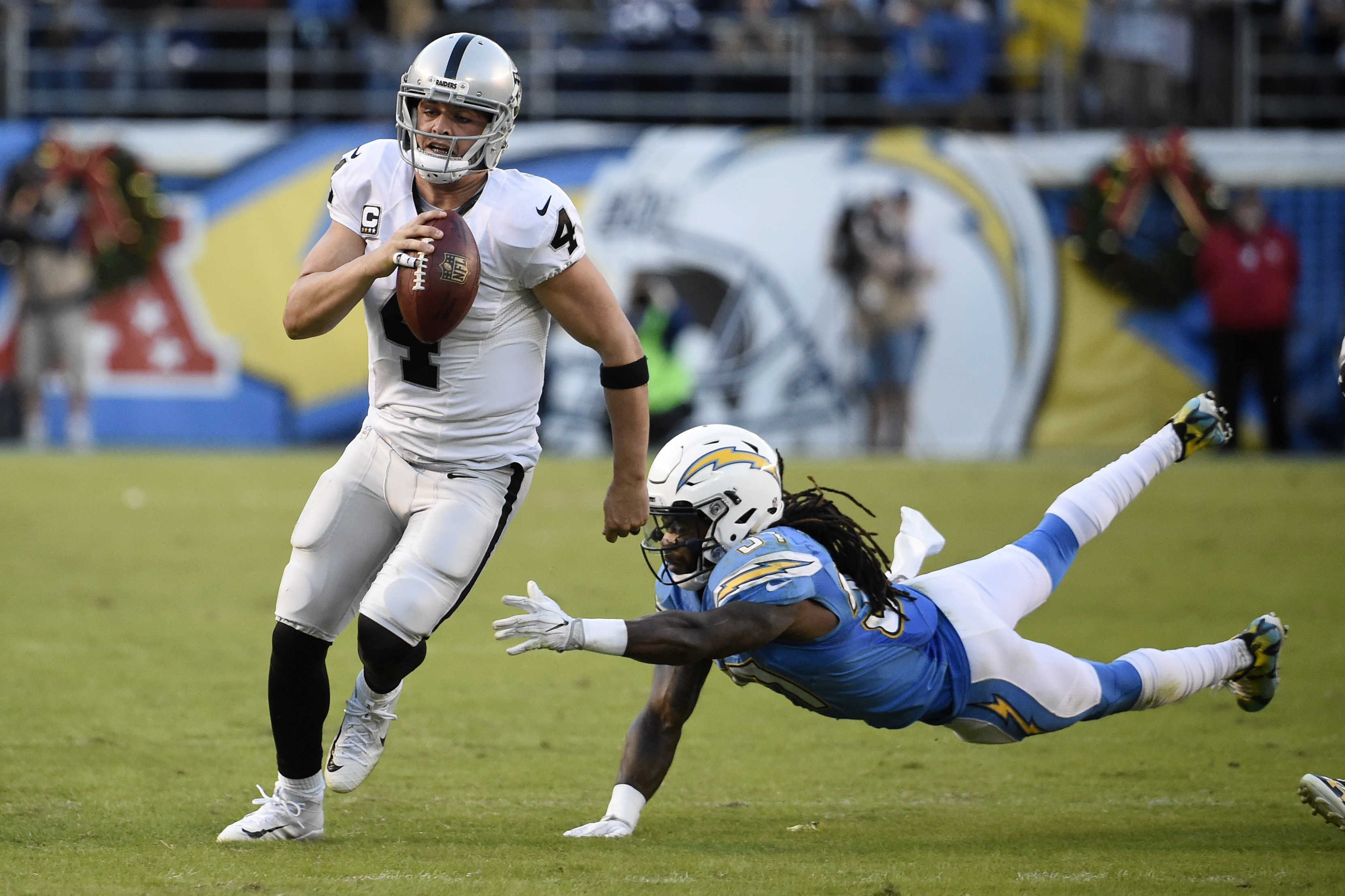 Oakland Raiders quarterback Derek Carr gets away from San Diego Chargers strong safety Jahleel Addae during the second half of an NFL football game Sunday, Dec. 18, 2016, in San Diego. (AP Photo/Denis Poroy)
