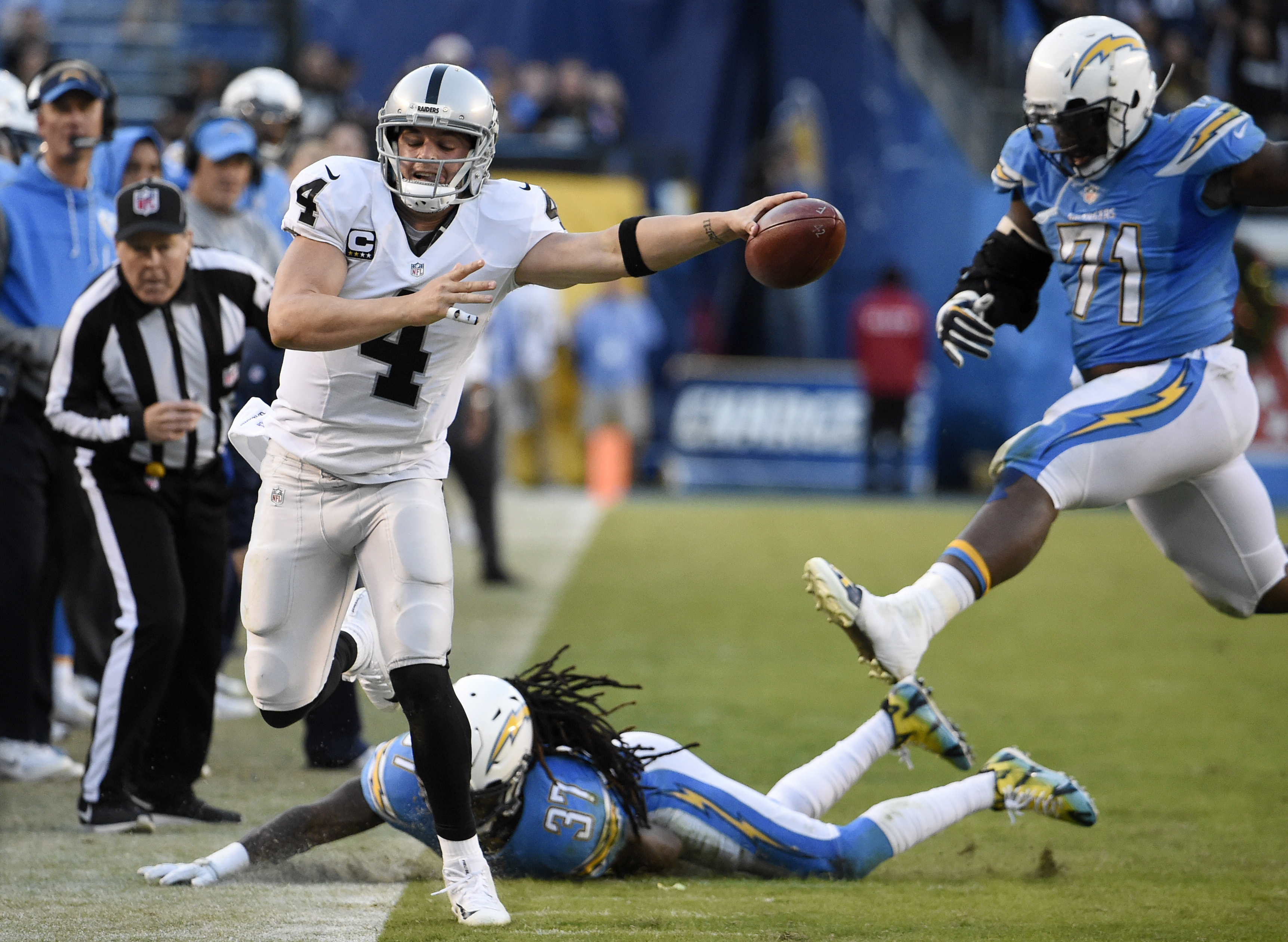 Oakland Raiders quarterback Derek Carr (4) reaches for a first down before going out of bounds as San Diego Chargers strong safety Jahleel Addae (37) and defensive tackle Kaleb Eulls (71) defend during the second half of an NFL football game Sunday, Dec.
