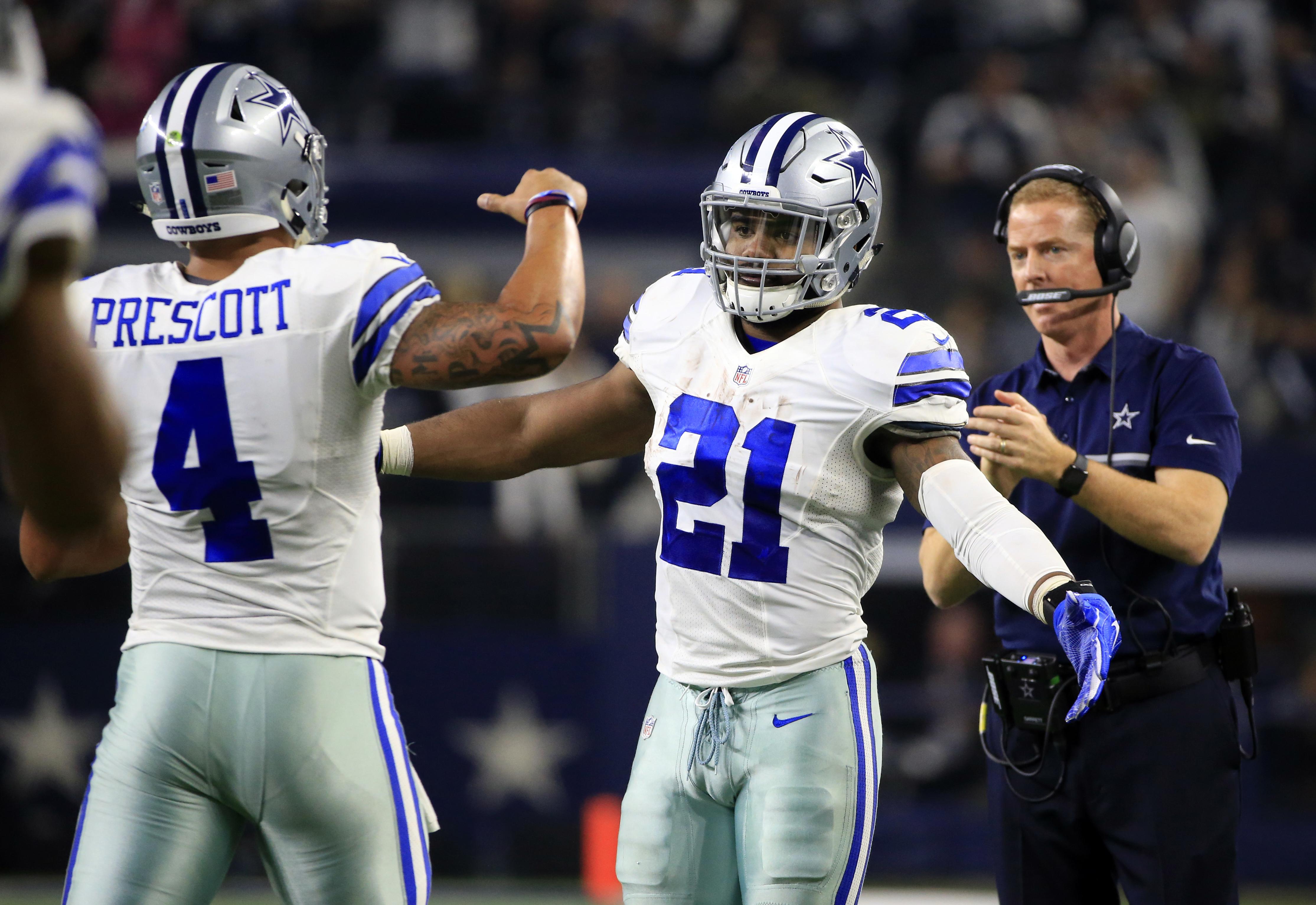 Dallas Cowboys' Dak Prescott (4) is congratulated on his touchdown run by Ezekiel Elliott (21) in the first half of an NFL football game against the Tampa Bay Buccaneers as head coach Jason Garrett, right, watches, , Sunday, Dec. 18, 2016, in Arlington, T