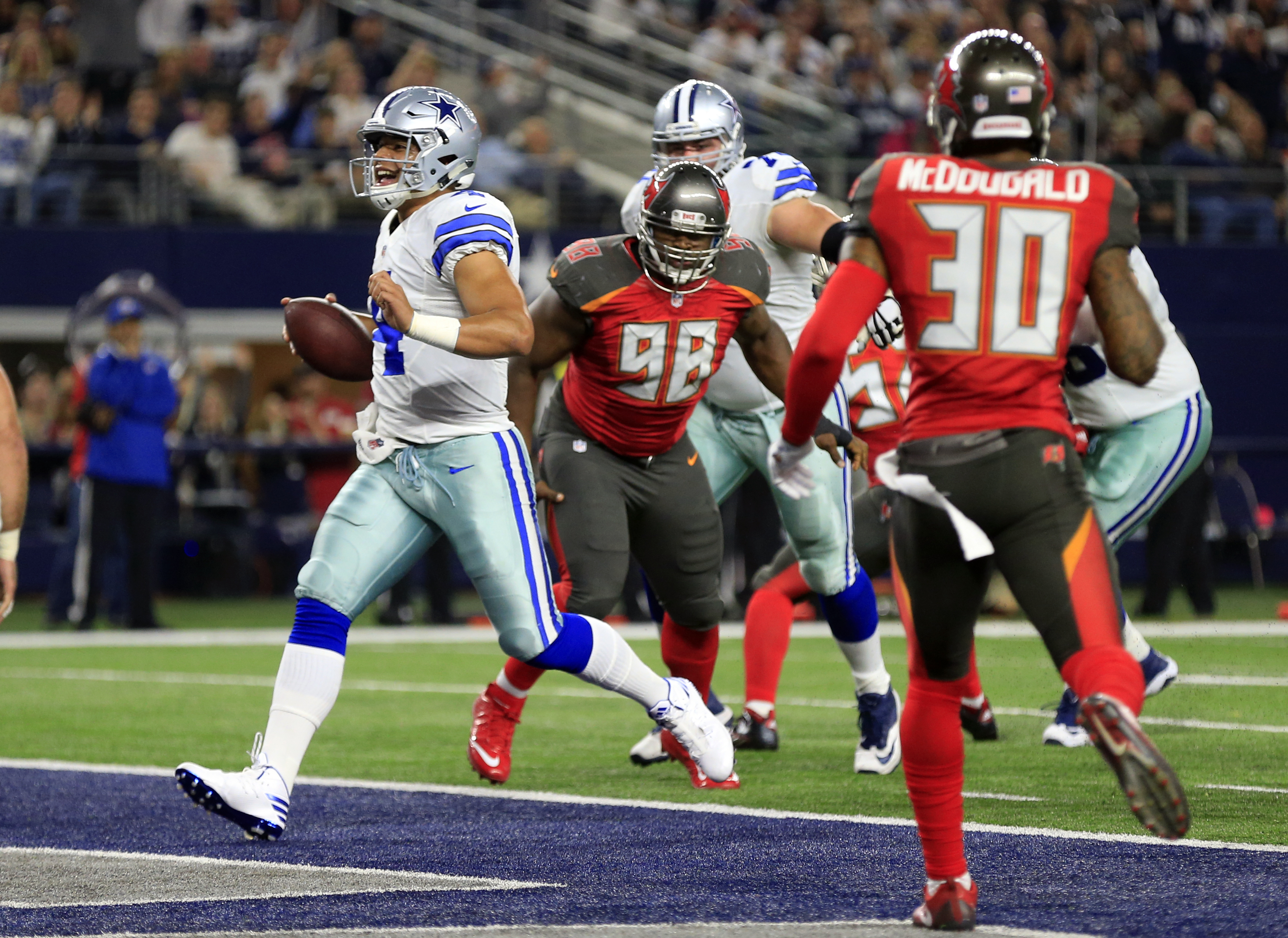 Dallas Cowboys quarterback Dak Prescott (4) breaks into the end zone for a touchdown as Clinton McDonald (98) and Bradley McDougald (30) watch in the first half of an NFL football game, Sunday, Dec. 18, 2016, in Arlington, Texas. (AP Photo/Ron Jenkins)