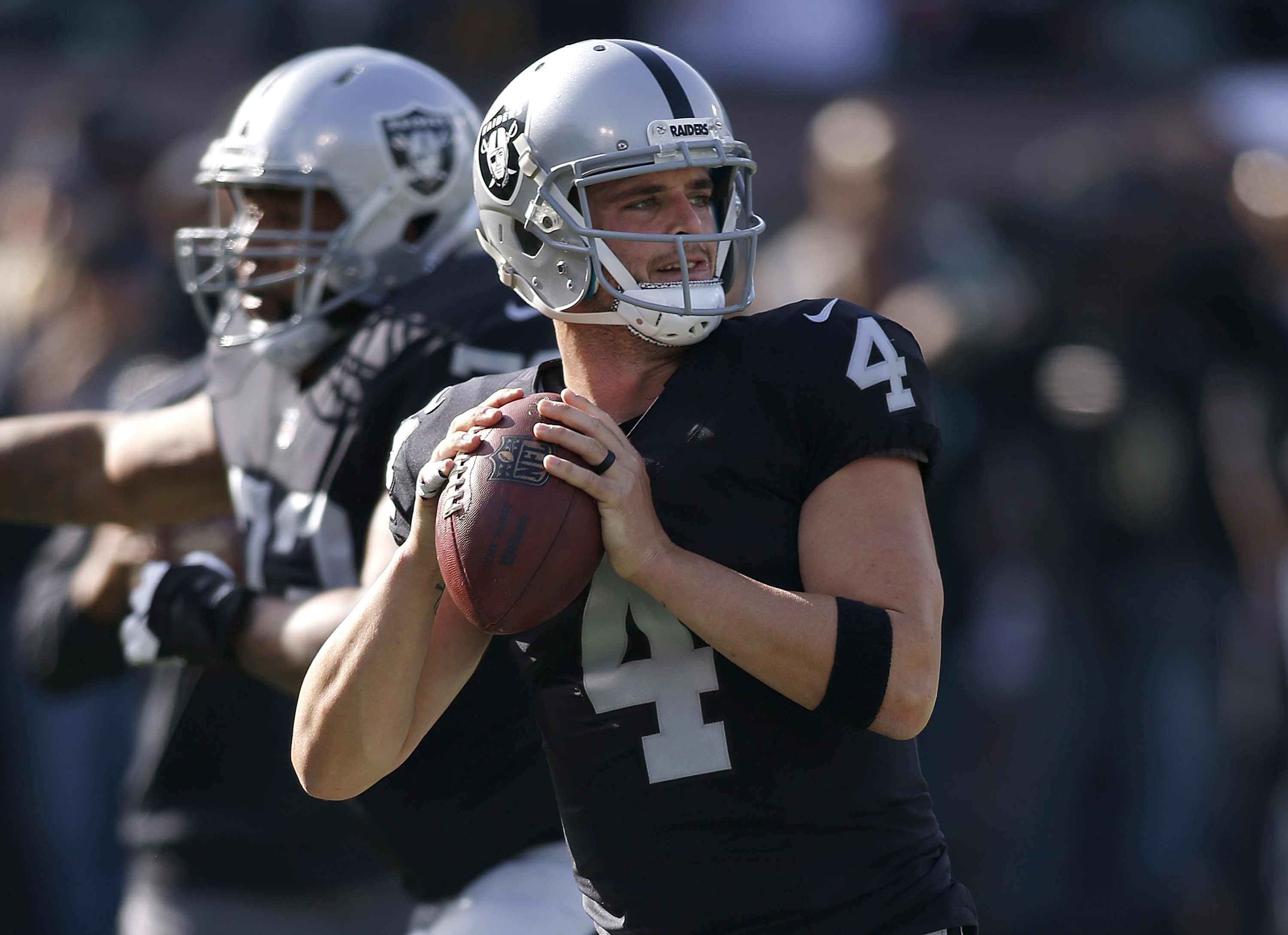 FILE - In this Sunday, Dec. 4, 2016 file photo, Oakland Raiders quarterback Derek Carr (4) warms up before an NFL football game against the Buffalo Bills in Oakland, Calif. This has not been the most watchable of NFL seasons, although the action and enter