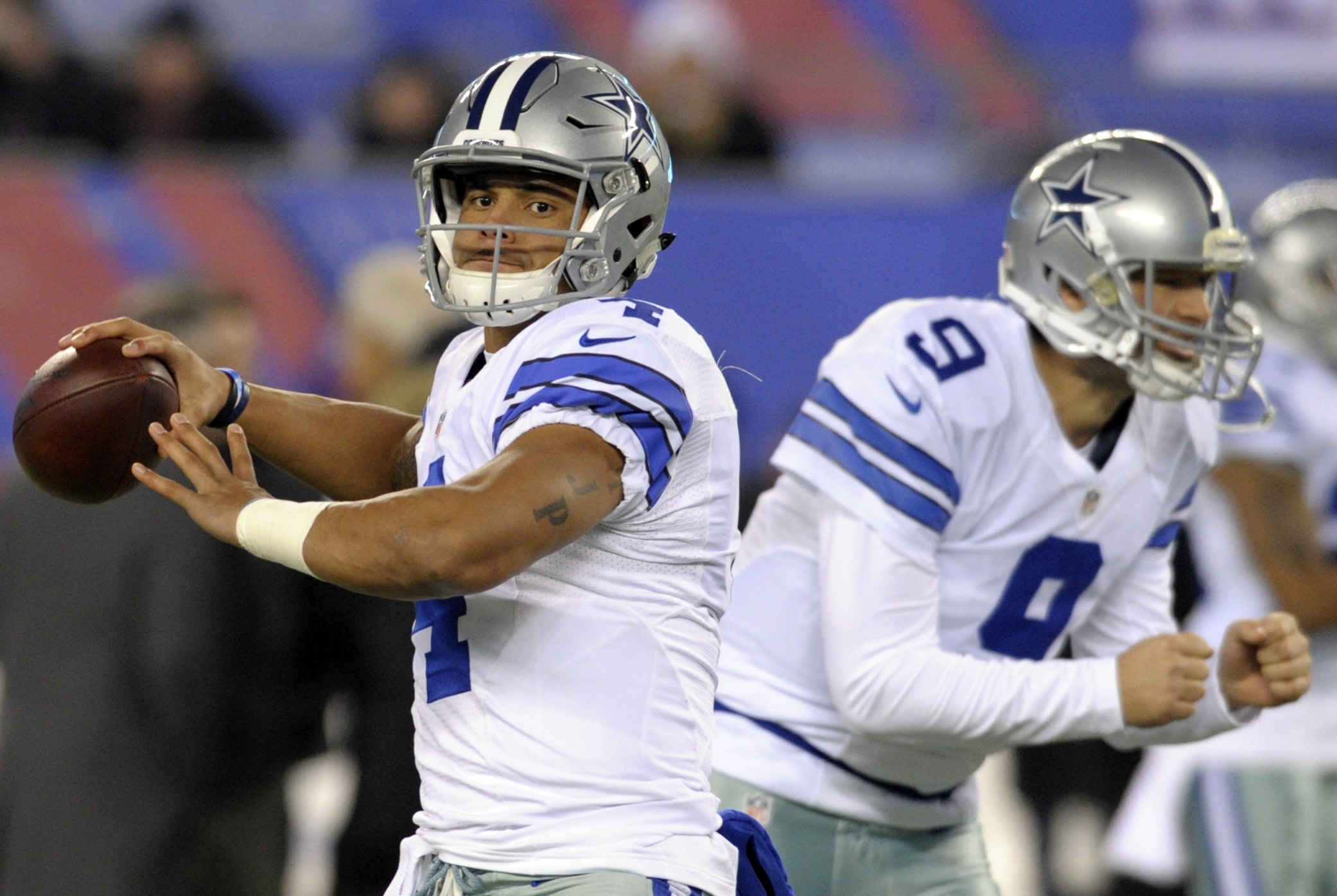 FILE - In this Sunday, Dec. 11, 2016 file photo, Dallas Cowboys quarterback Dak Prescott (4) and Tony Romo (9) warm up before an NFL football game against the New York Giants in East Rutherford, N.J. The Cowboys play the Detroit Lions on Monday, Dec. 26,