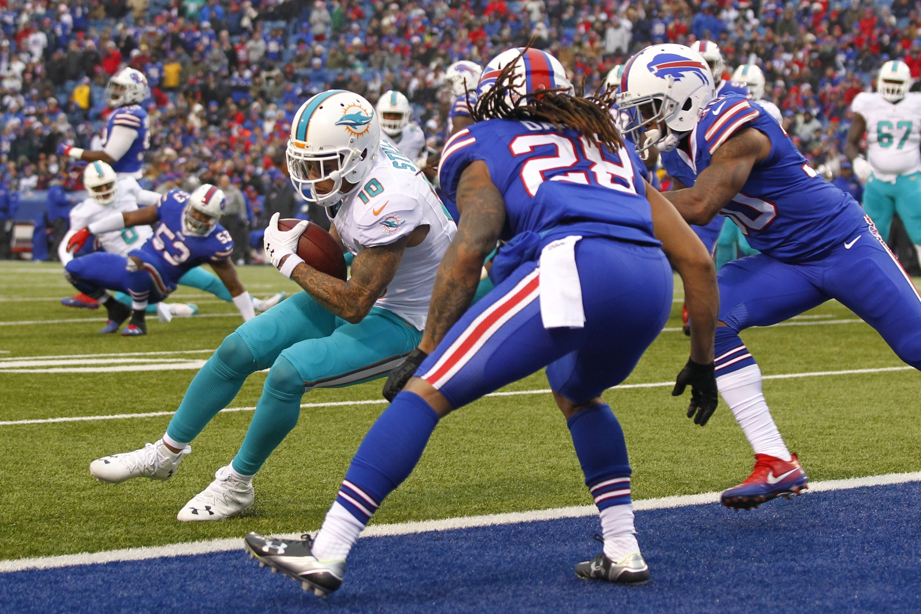 Miami Dolphins wide receiver Kenny Stills (10) scores a touchdown in front of Buffalo Bills' Ronald Darby (28) as quarterback Matt Moore (8) watches him during the second half of an NFL football game, Saturday, Dec. 24, 2016, in Orchard Park, N.Y. (AP Pho