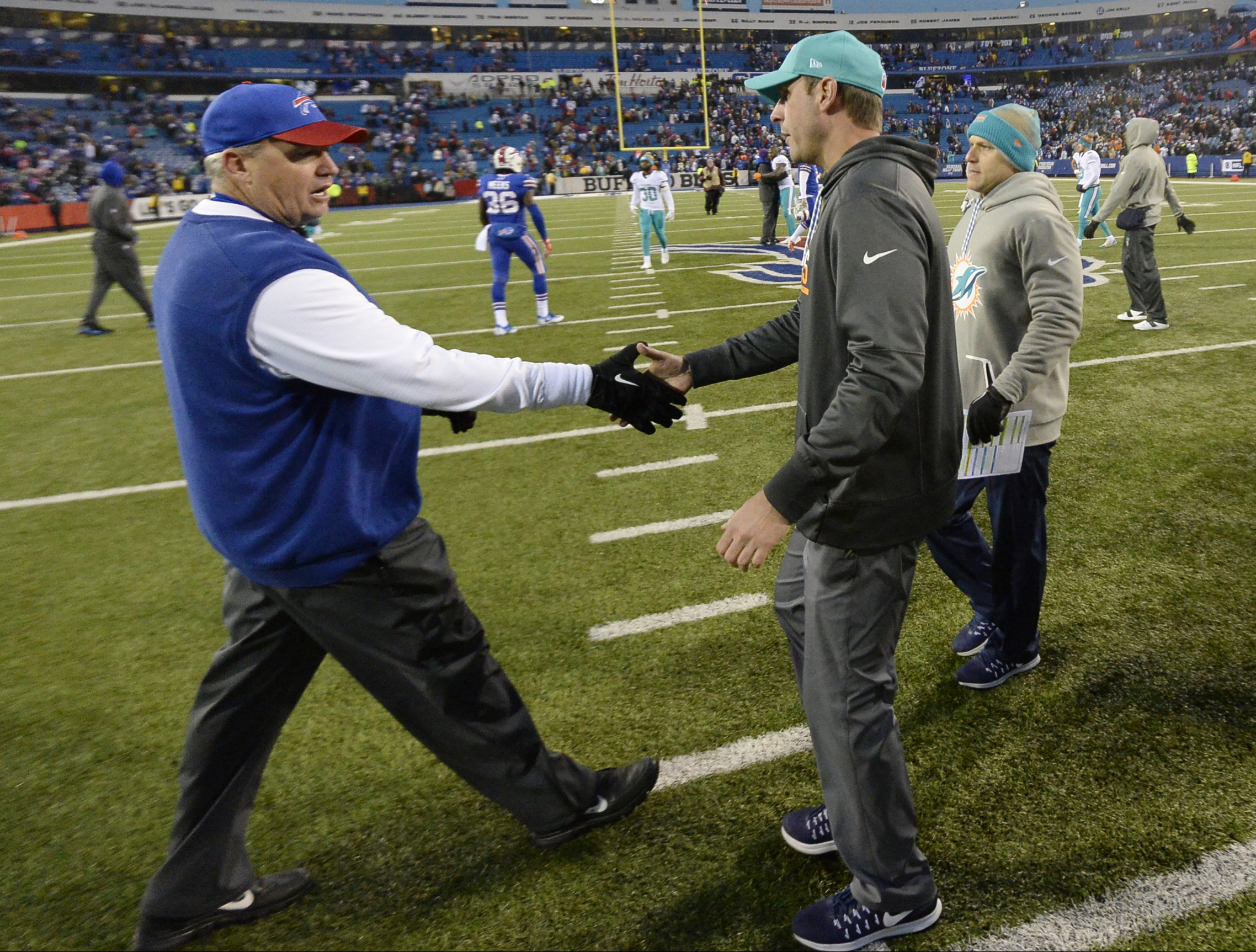 Buffalo Bills head coach Rex Ryan, left, shakes hands with Miami Dolphins head coach Adam Gase, right, after an NFL football game Saturday, Dec. 24, 2016, in Orchard Park, N.Y. The Dolphins won 34-31. (AP Photo/Adrian Kraus)