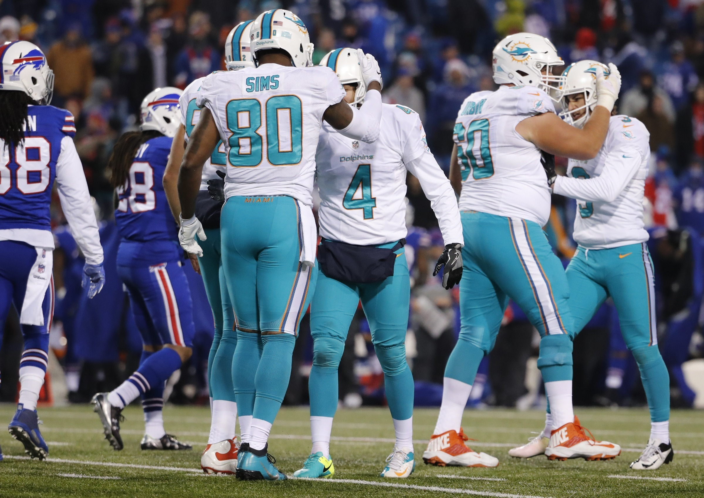 Miami Dolphins celebrate after kicker Andrew Franks (3) made the winning goal in overtime of an NFL football game against the Buffalo Bills in Orchard Park, N.Y., Saturday, Dec. 24, 2016. (Al Diaz/Miami Herald via AP)