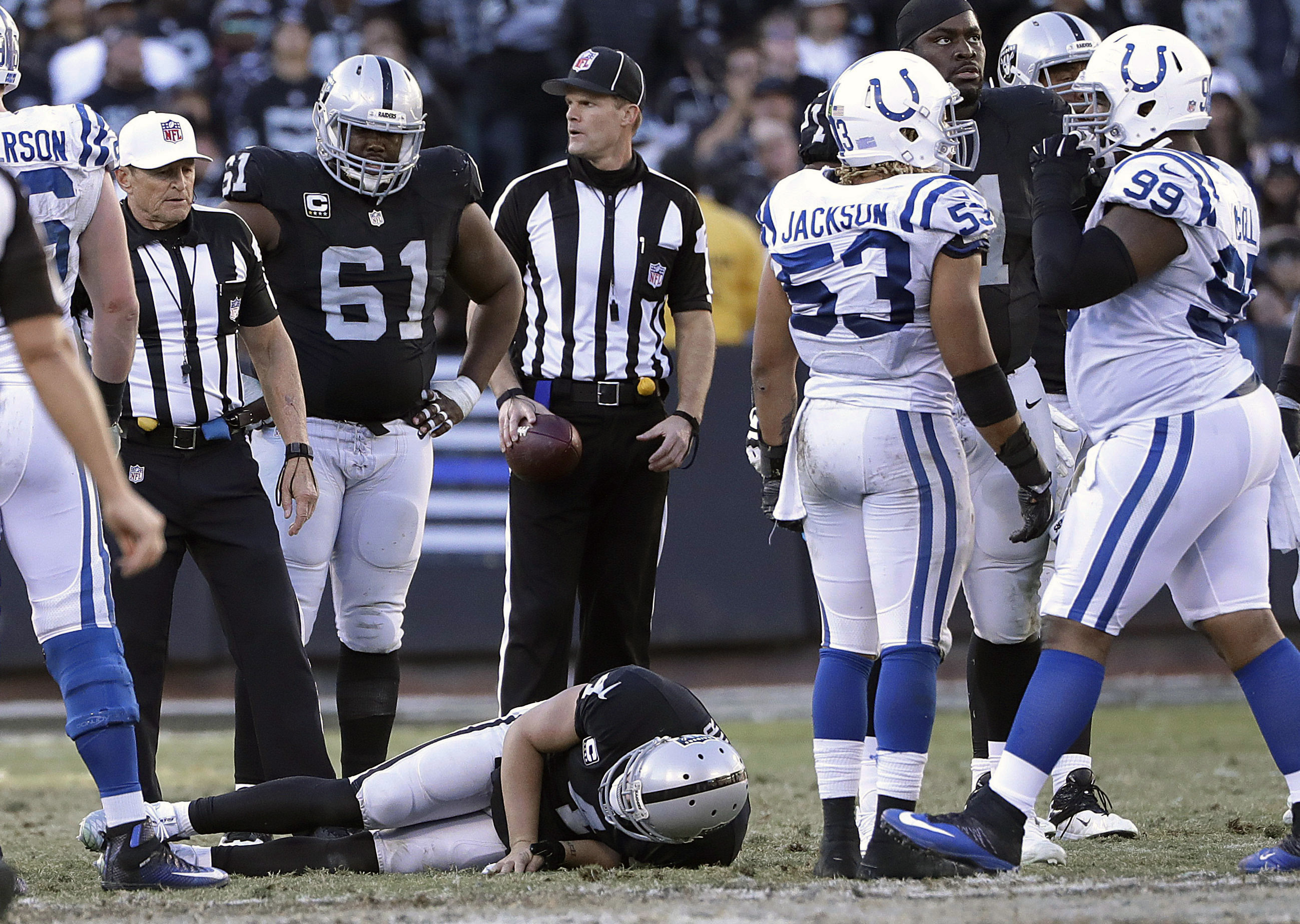 Oakland Raiders quarterback Derek Carr, bottom, remains on the field after being tackled by Indianapolis Colts inside linebacker Edwin Jackson during the second half of an NFL football game in Oakland, Calif., Saturday, Dec. 24, 2016. (AP Photo/Marcio Jos