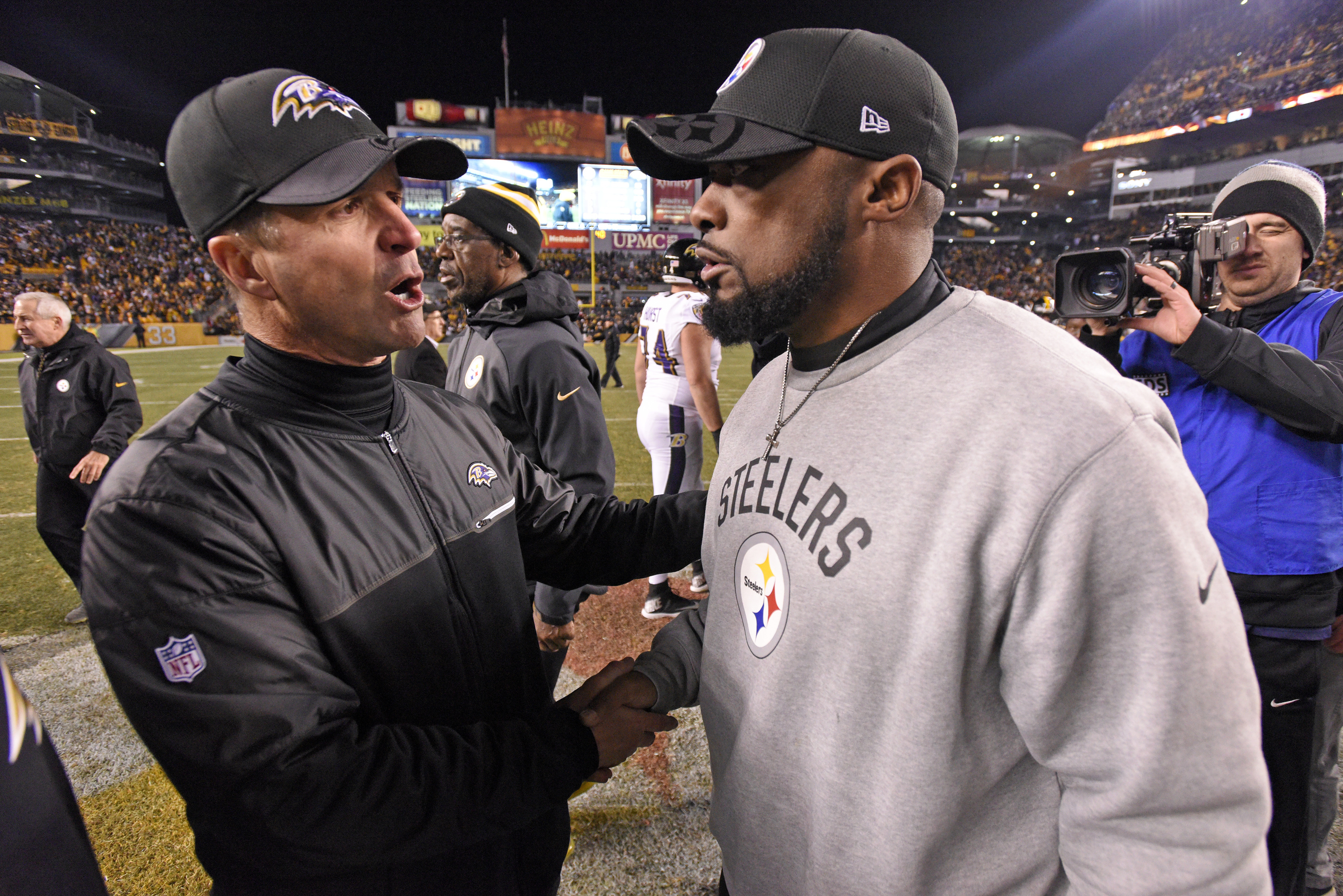 Pittsburgh Steelers head coach Mike Tomlin, right, and Baltimore Ravens head coach John Harbaugh meet following an NFL football game in Pittsburgh, Sunday, Dec. 25, 2016. The Steelers won 31-27. (AP Photo/Don Wright)