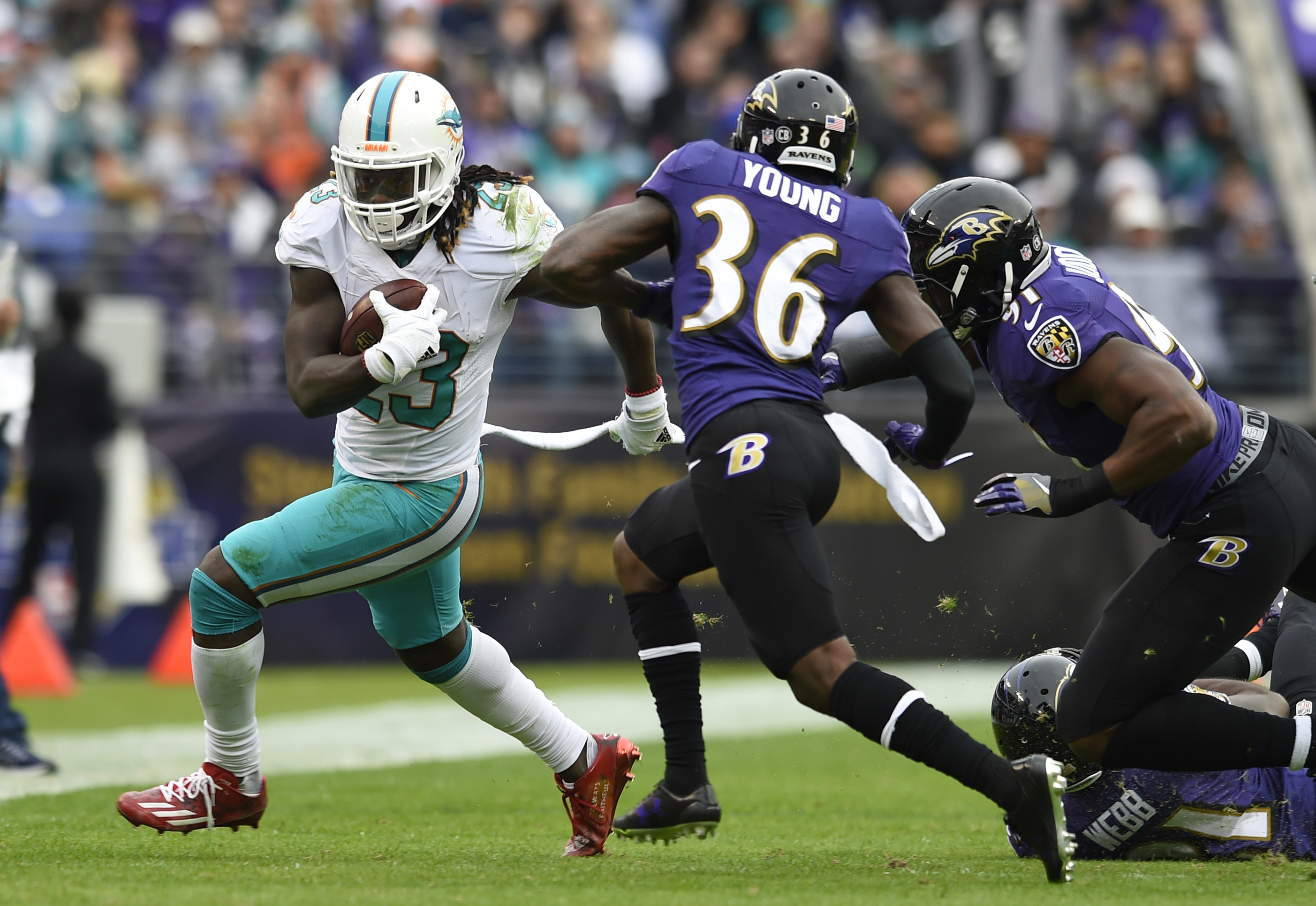 FILE - In this Dec. 4, 2016, file photo, Miami Dolphins running back Jay Ajayi, left, rushes past Baltimore Ravens cornerback Tavon Young (36) and linebacker Matt Judon during an NFL football game in Baltimore. Ajayi has had three 200-yard games this seas