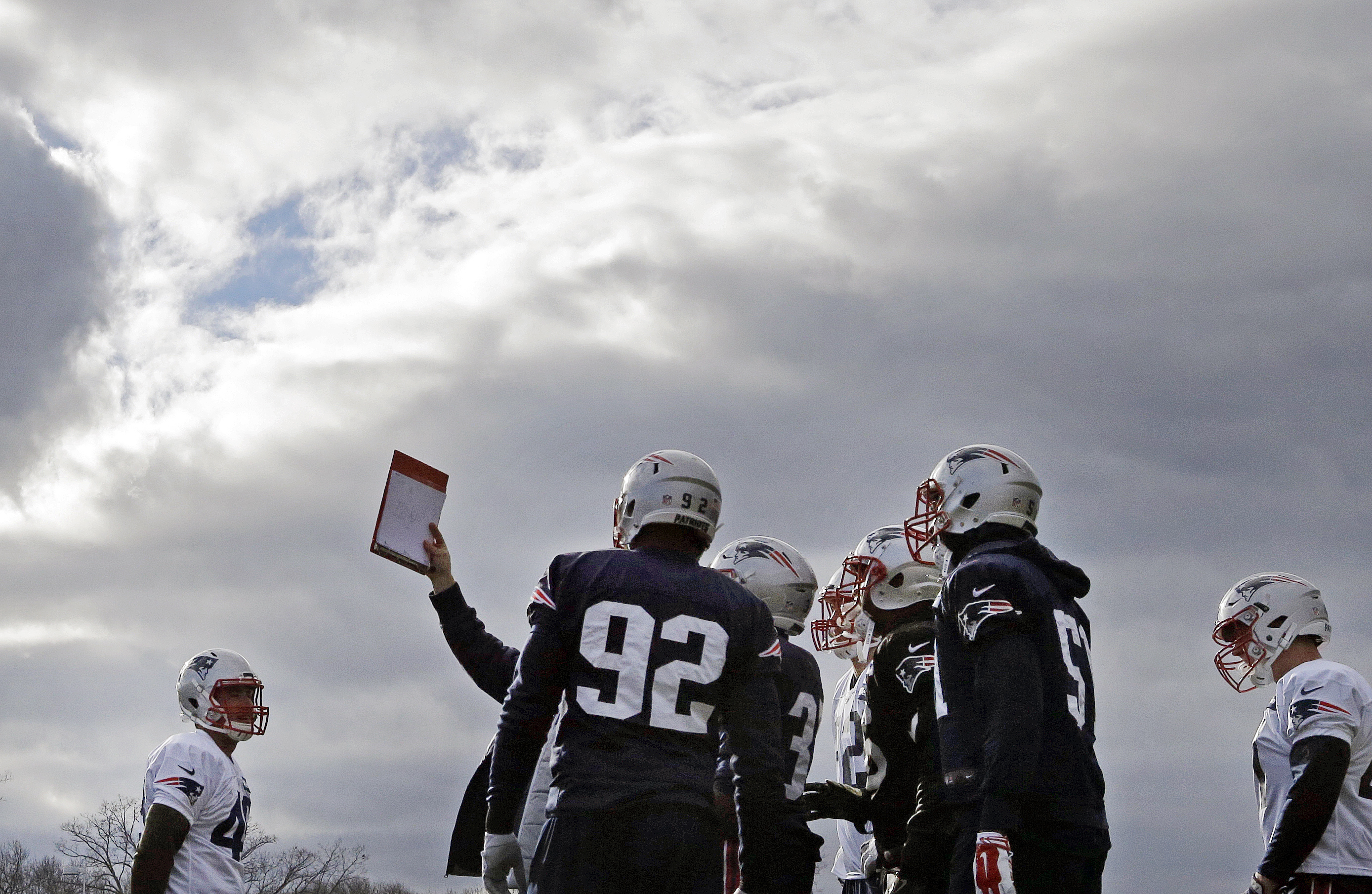 New England Patriots players huddle to look at a playbook during NFL football practice, Wednesday, Dec. 28, 2016, in Foxborough, Mass. (AP Photo/Elise Amendola)