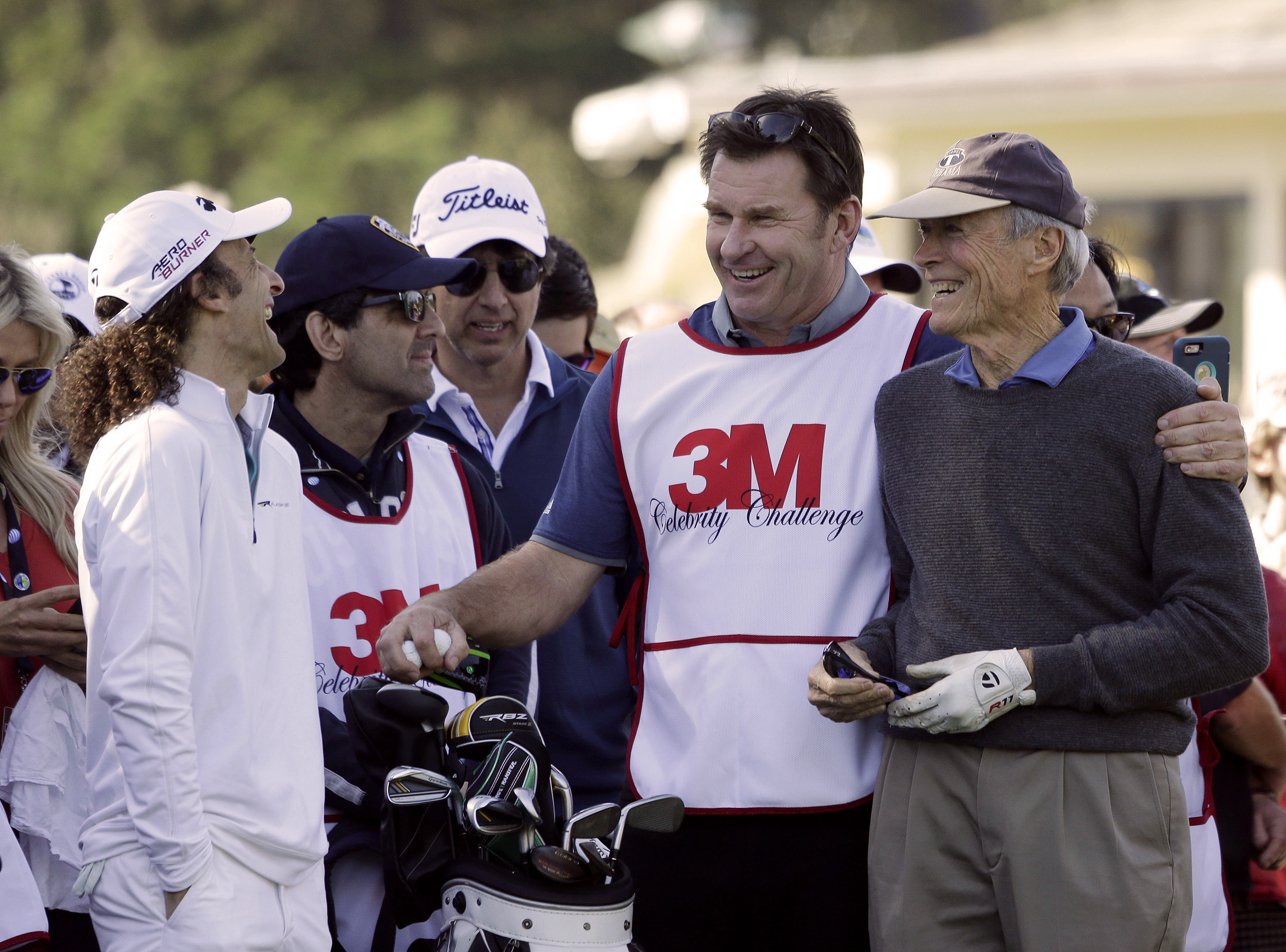 Musician Kenny G, left, laughs as actor Clint Eastwood, right, is embraced by his caddie Nick Faldo, second from right, on the first tee of the Pebble Beach Golf Links during the celebrity challenge event of the AT&T Pebble Beach National Pro-Am golf tour