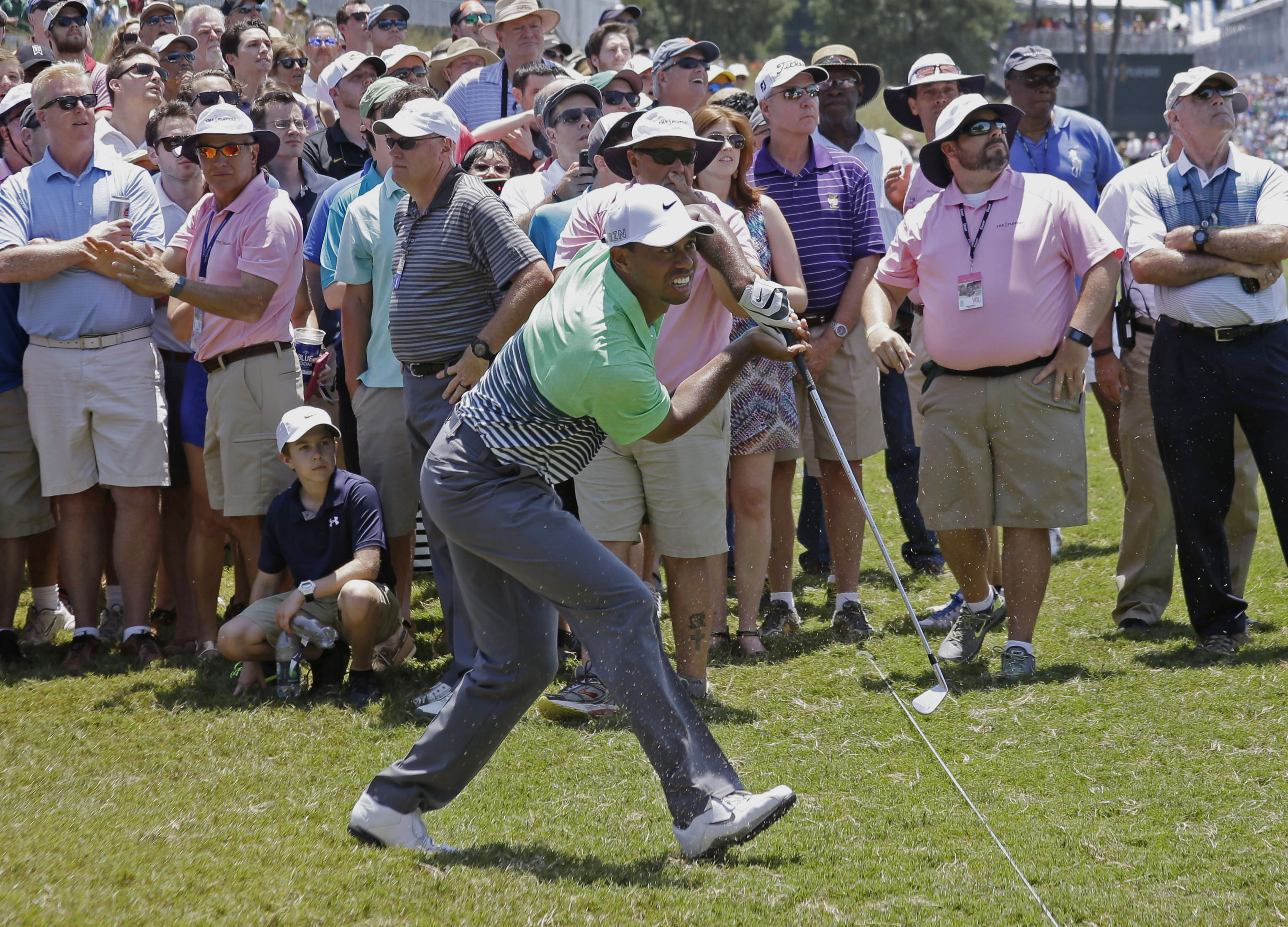 Tiger Woods follows his shot from the rough on the 18th fairway during the third round of The Players Championship golf tournament Saturday, May 9, 2015, in Ponte Vedra Beach, Fla. (AP Photo/John Raoux)