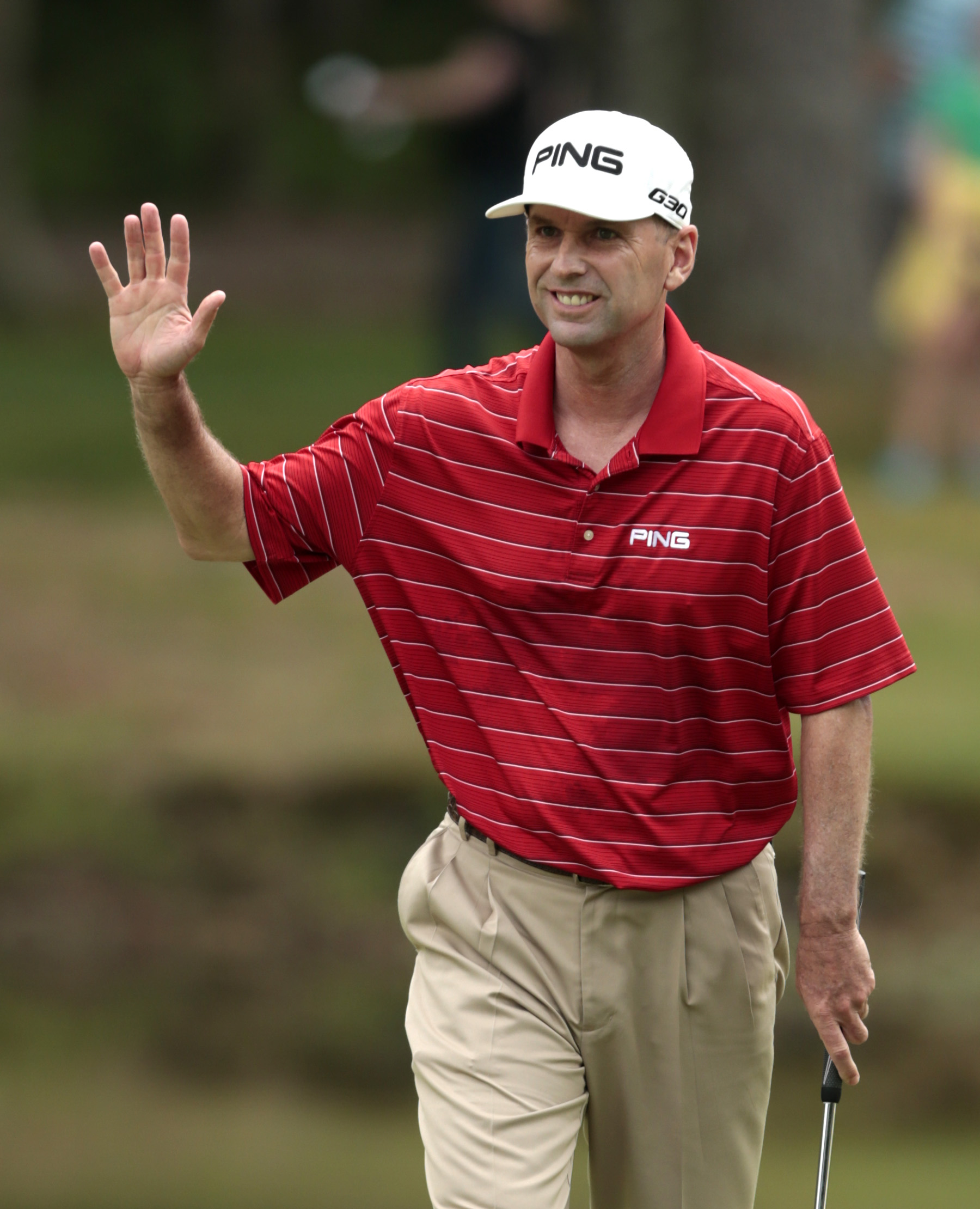Kevin Sutherland waves to fans after making a birdie putt on the ninth hole during the Regions Tradition Champions Tour golf tournament at Shoal Creek Country Club, Saturday, May 16, 2015, in Birmingham, Ala. (AP Photo/Butch Dill)