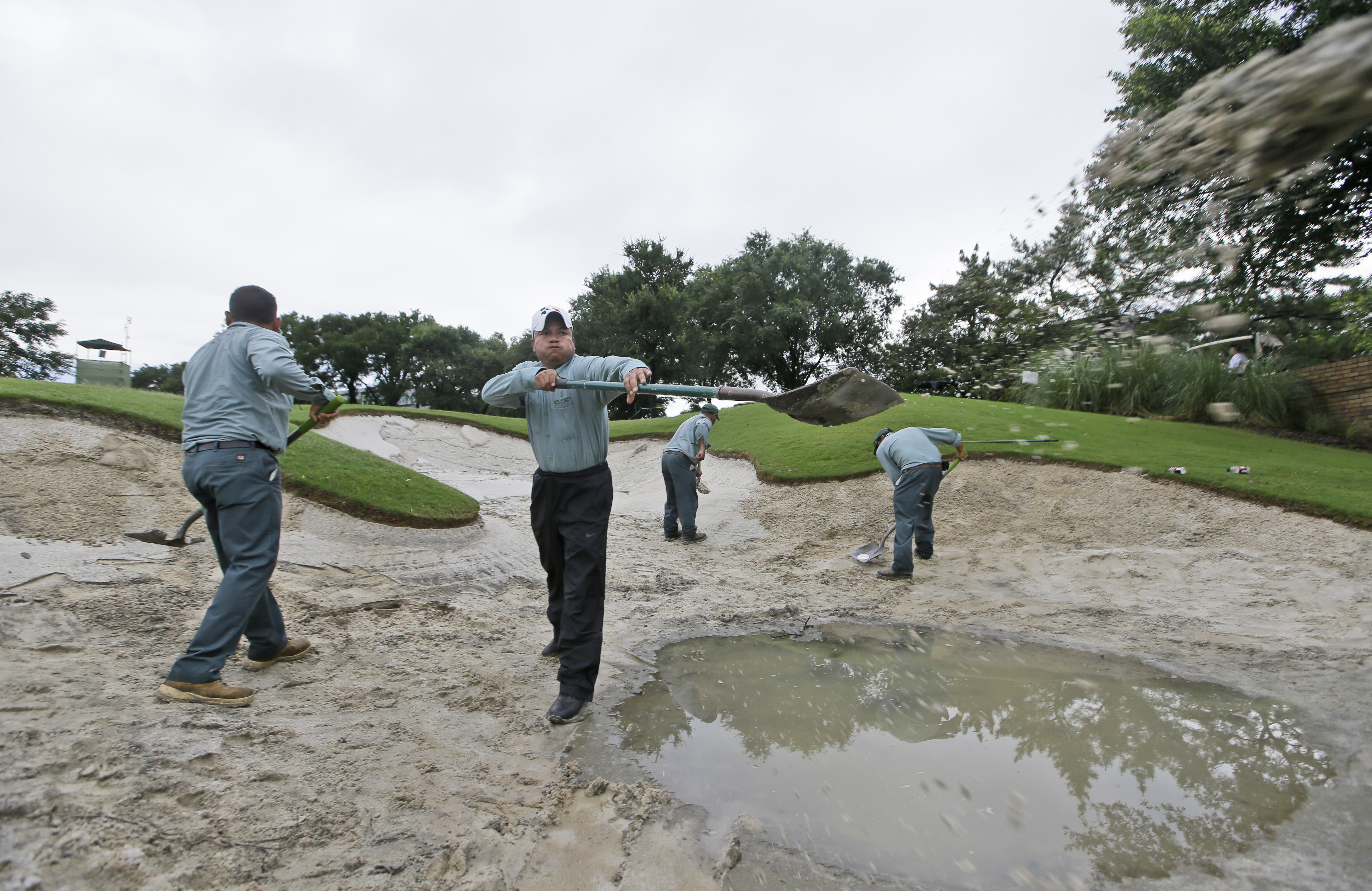 Grounds keepers work to repair a sand trap on the ninth green before the start of the second round of the Byron Nelson golf tournament, Friday, May 29, 2015, in Irving, Texas. Heavy overnight rains delayed the start of play. (AP Photo/LM Otero)