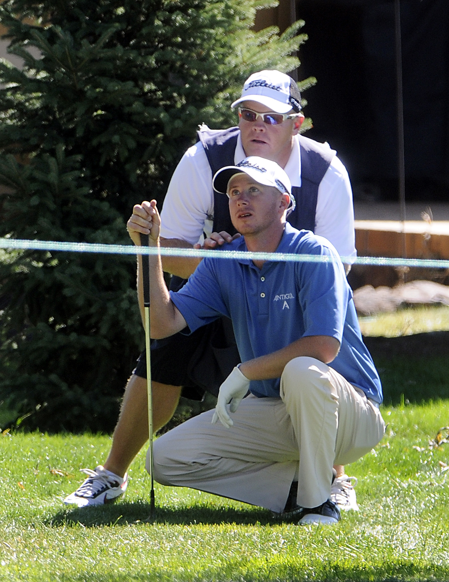 Tyler Aldridge, front, of Nampa, Idaho, checks out the low tree branches he needs to negotiate with help from his caddie Thursday morning, Sept. 11, 2008, on the 12th fairway in the first round of the Nationwide Tour's Boise Open golf tournament in Boise,