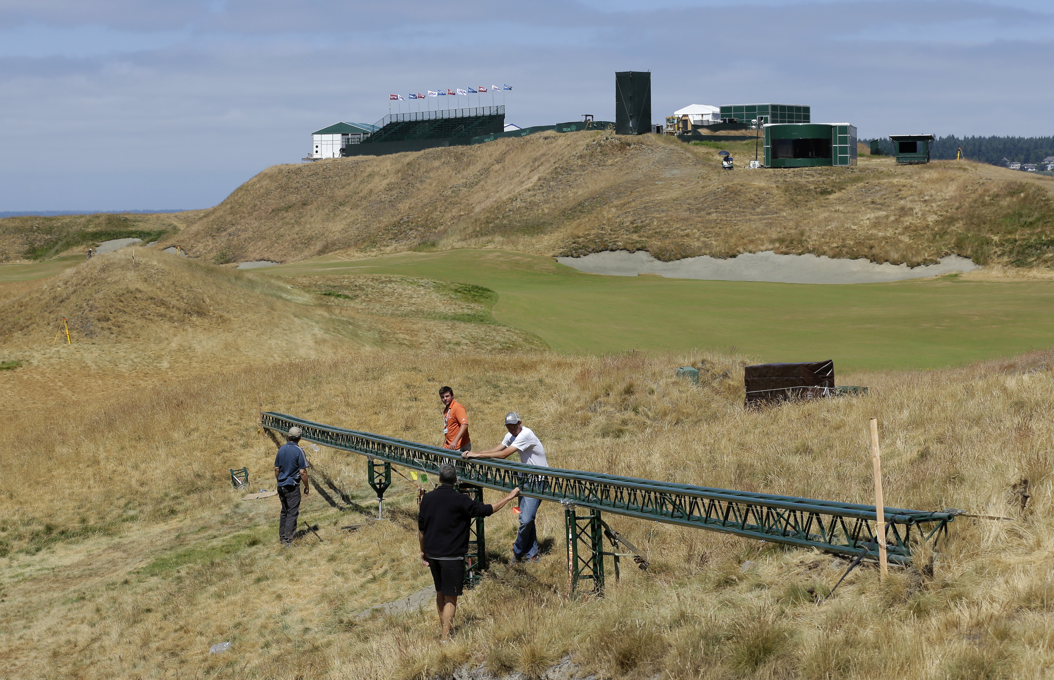 Technicians adjust a long video camera slider rail Thursday, June 11, 2015, on the 18th hole at Chambers Bay golf course in University Place, Wash. In its bid to take over the U.S. Open from NBC, Fox promised innovative coverage and will feature new graph