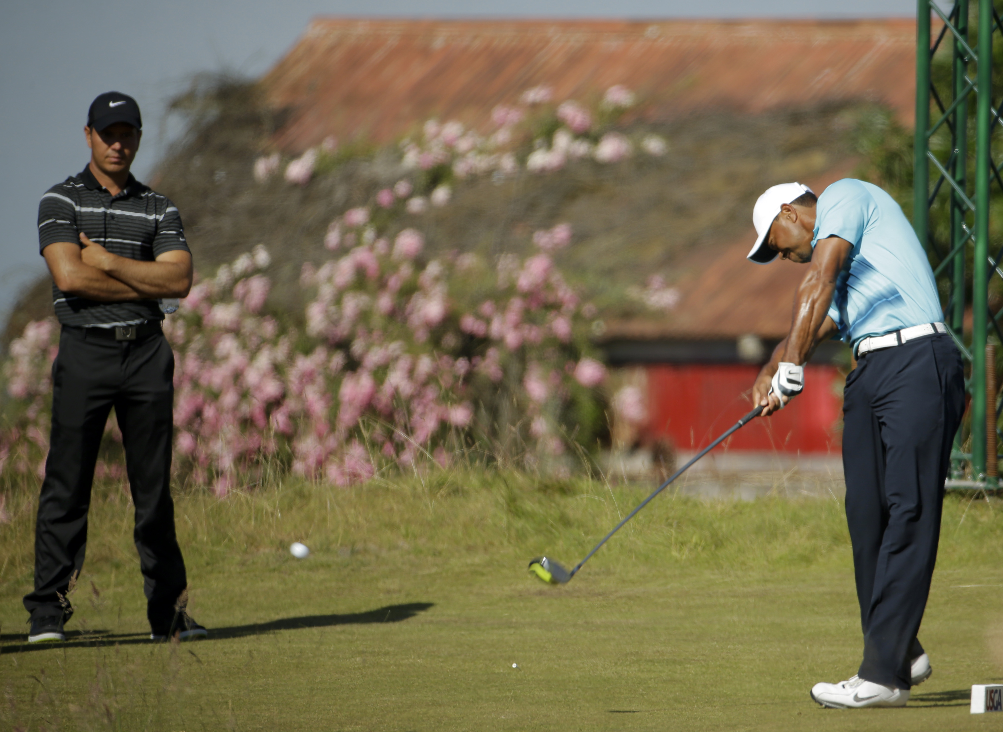 Tiger Wood, right, hits his tee shot on the 17th hole as Jason Day, of Australia, looks on during a practice round for the U.S. Open golf tournament at Chambers Bay, Monday, June 15, 2015, in University Place, Wash. (AP Photo/Ted S. Warren)