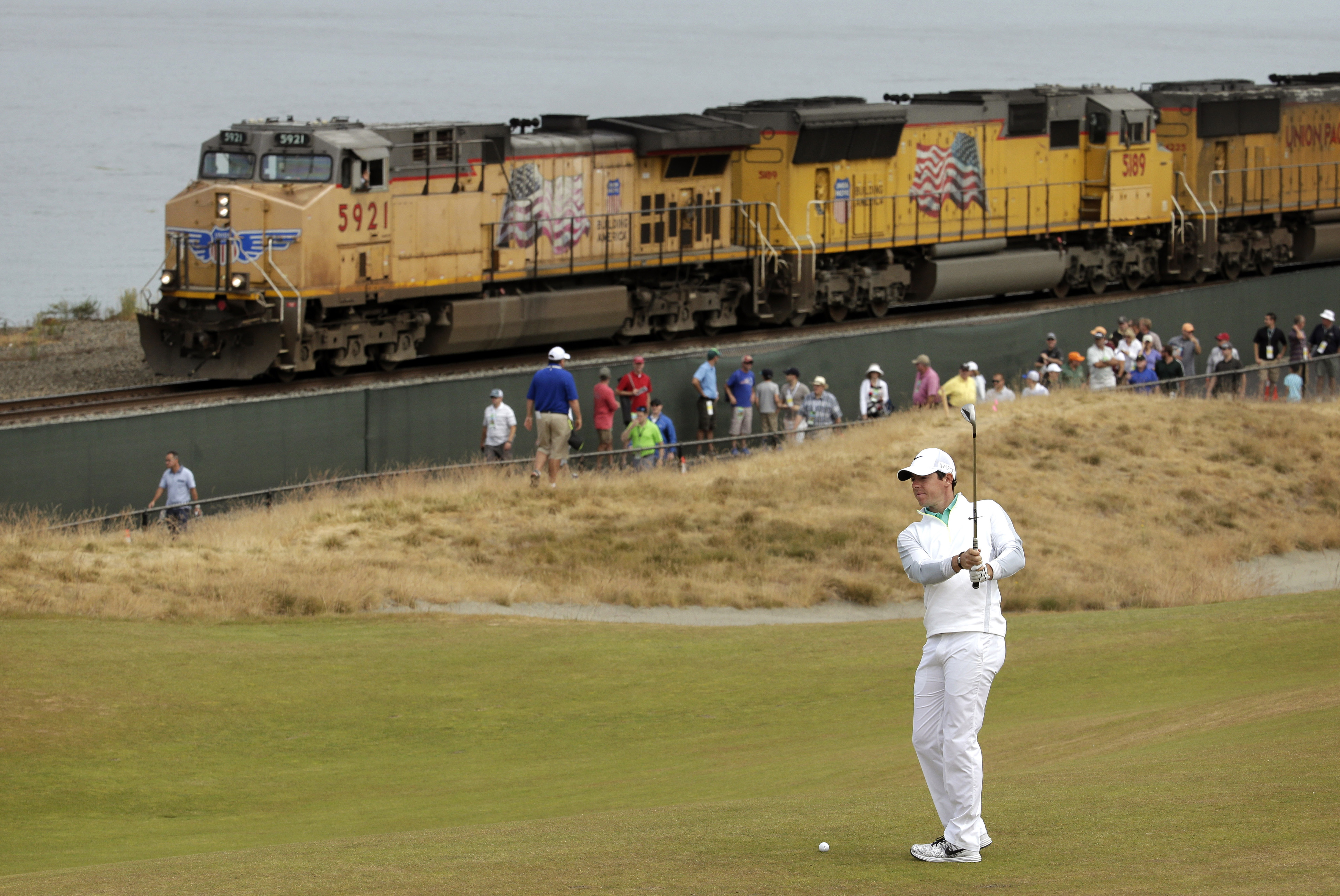 Rory McIlroy, of Northern Ireland, prepares to hit from the 16th fairway as a fright train rolls past during the first round of the U.S. Open golf tournament at Chambers Bay on Thursday, June 18, 2015 in University Place, Wash. (AP Photo/Charlie Riedel)