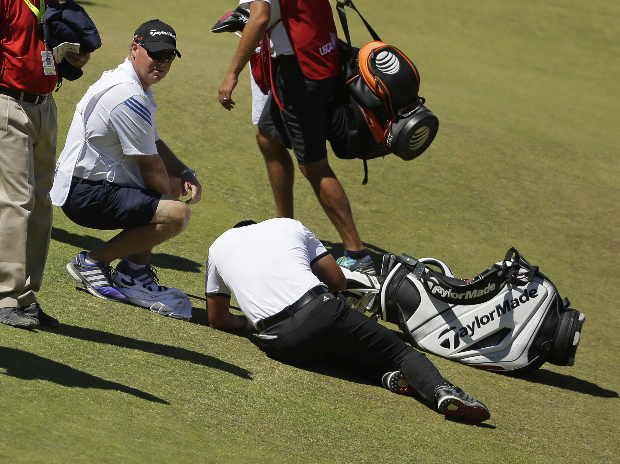 Jason Day, of Australia, lies in the fairway after falling down as his caddie Colin Swatton crouches beside him on the ninth hole during the second round of the U.S. Open golf tournament at Chambers Bay on Friday, June 19, 2015 in University Place, Wash.