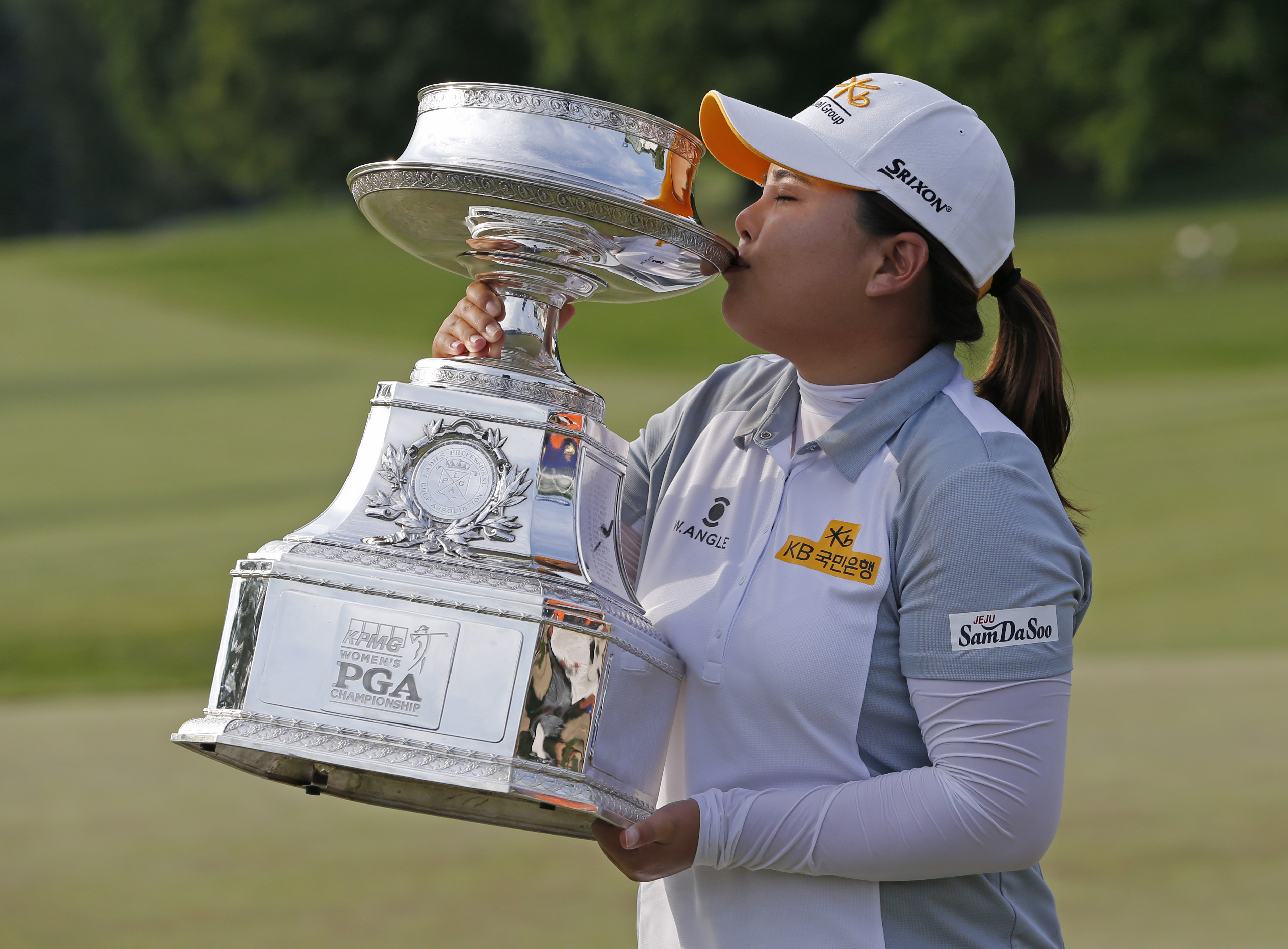 Inbee Park, of South Korea, kisses the trophy after winning the KPMG Women's PGA golf championship at Westchester Country Club in Harrison, N.Y., Sunday, June 14, 2015. (AP Photo/Julio Cortez)
