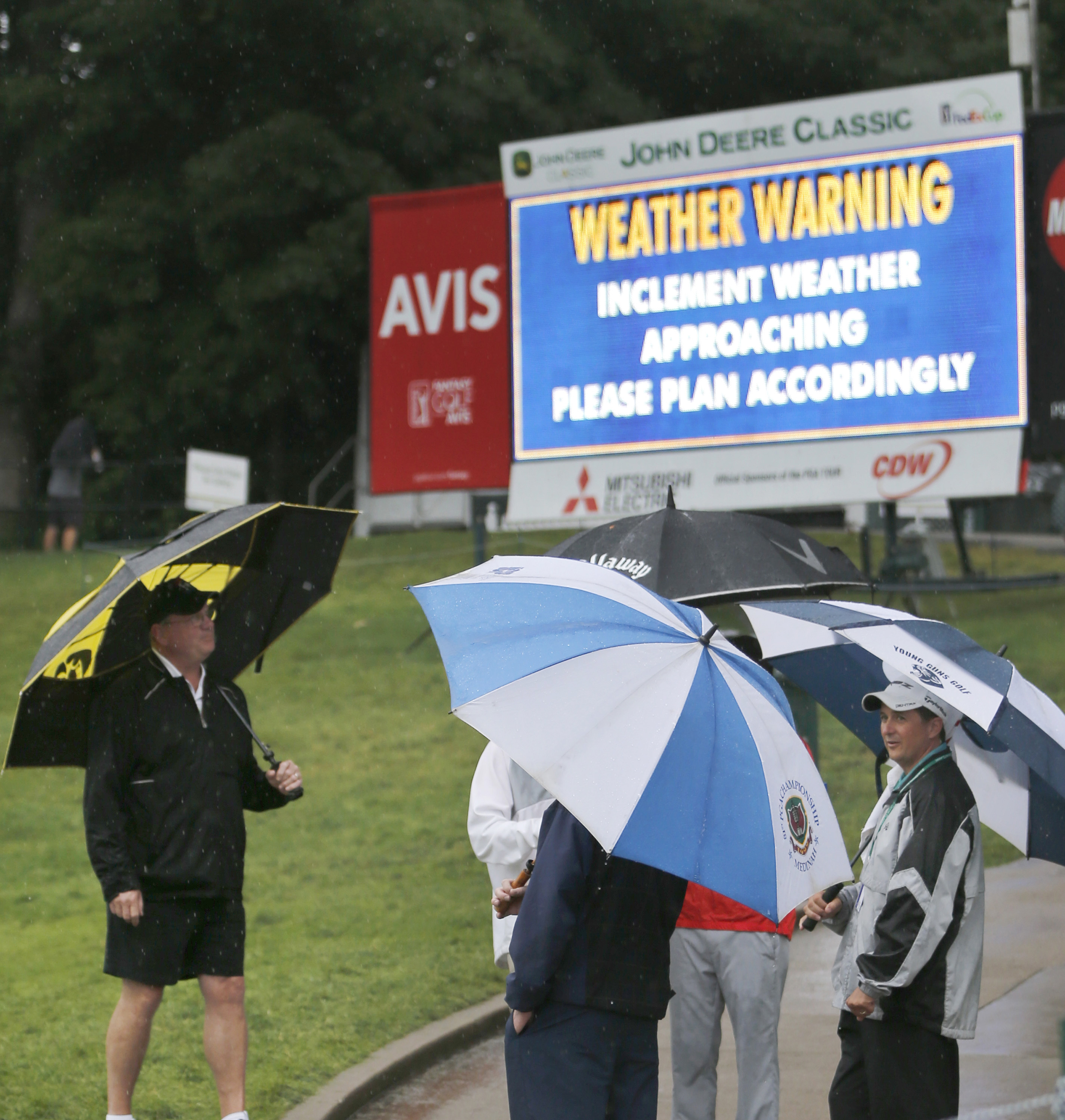 Spectators stand around the 18th green as a severe weather warning is posted on the scoreboard during a rain delay at the third round of the John Deere Classic golf tournament, Saturday, July 11, 2015, in Silvis, Ill. (AP Photo/Charles Rex Arbogast)