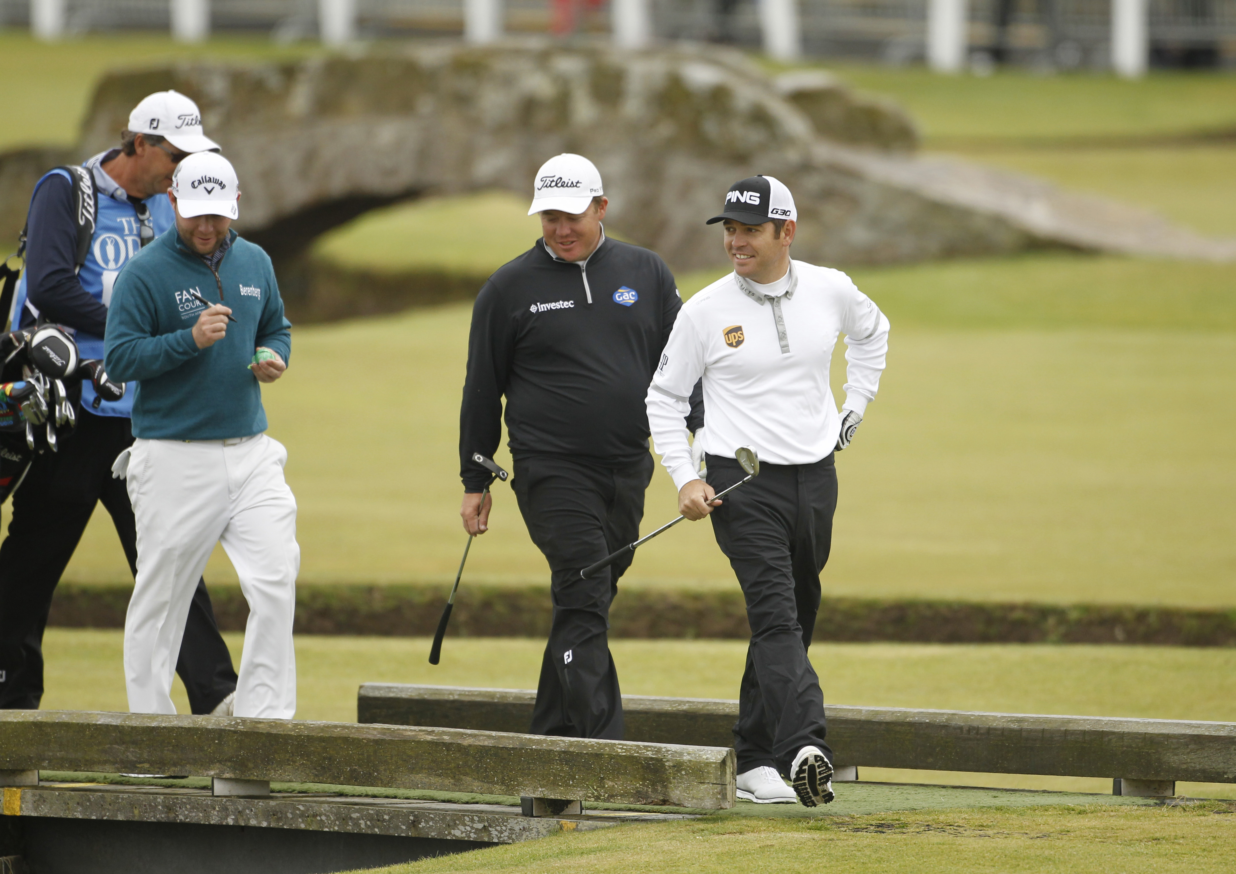 South Africa's George Coetzee, centre, Louis Oosthuizen, right, and Branden Grace walk towards the 1st green during a practice round  at the Old Course, St Andrews, Scotland, Monday, July 13, 2015. The  2015 Open Golf Championship that is due to take plac