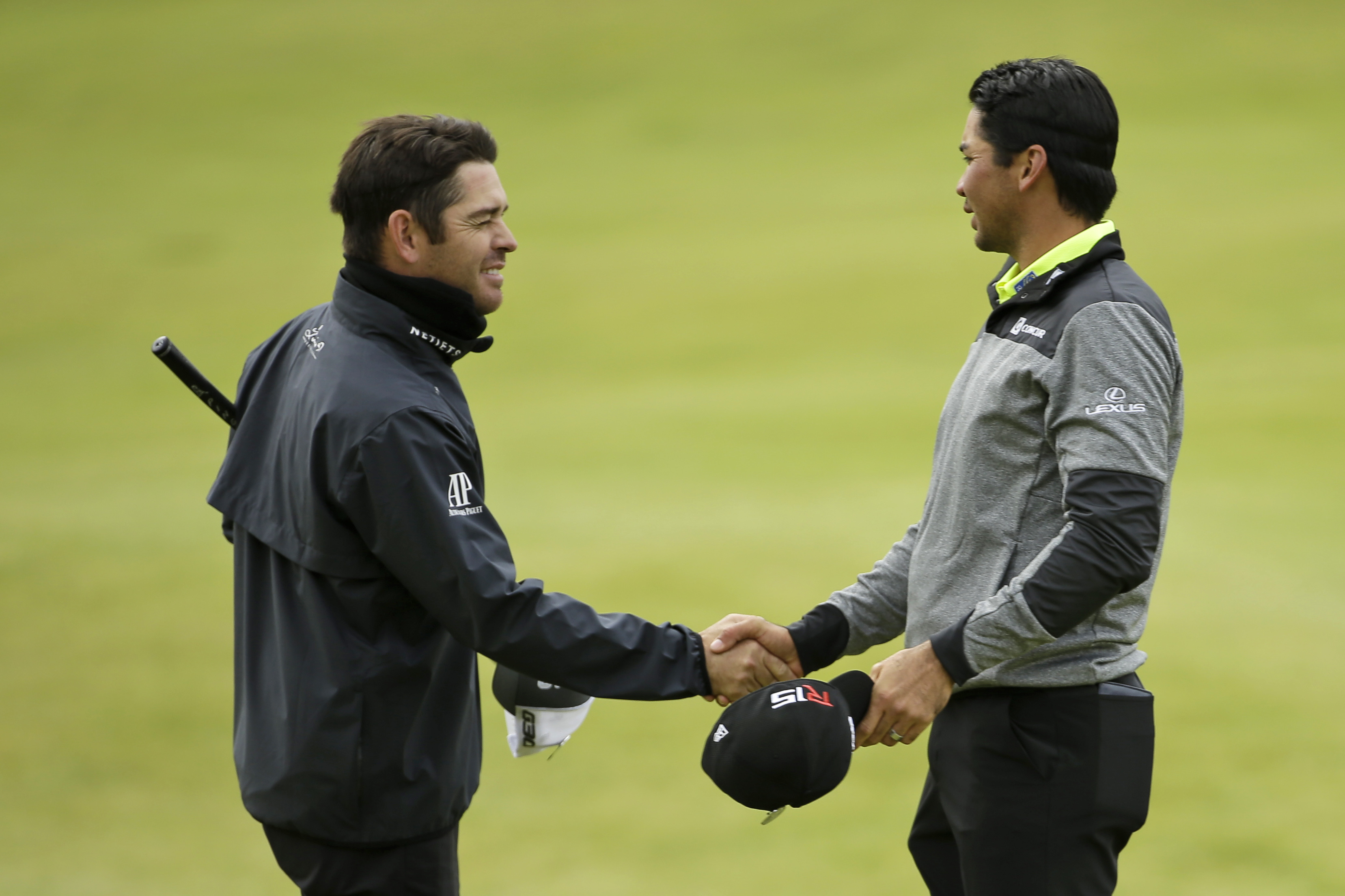 Australia's Jason Day, right, shakes hands with South Africa' Louis Oosthuizen on the 18th green following their round during the first round of the British Open Golf Championship at the Old Course, St. Andrews, Scotland, Thursday, July 16, 2015. (AP Phot
