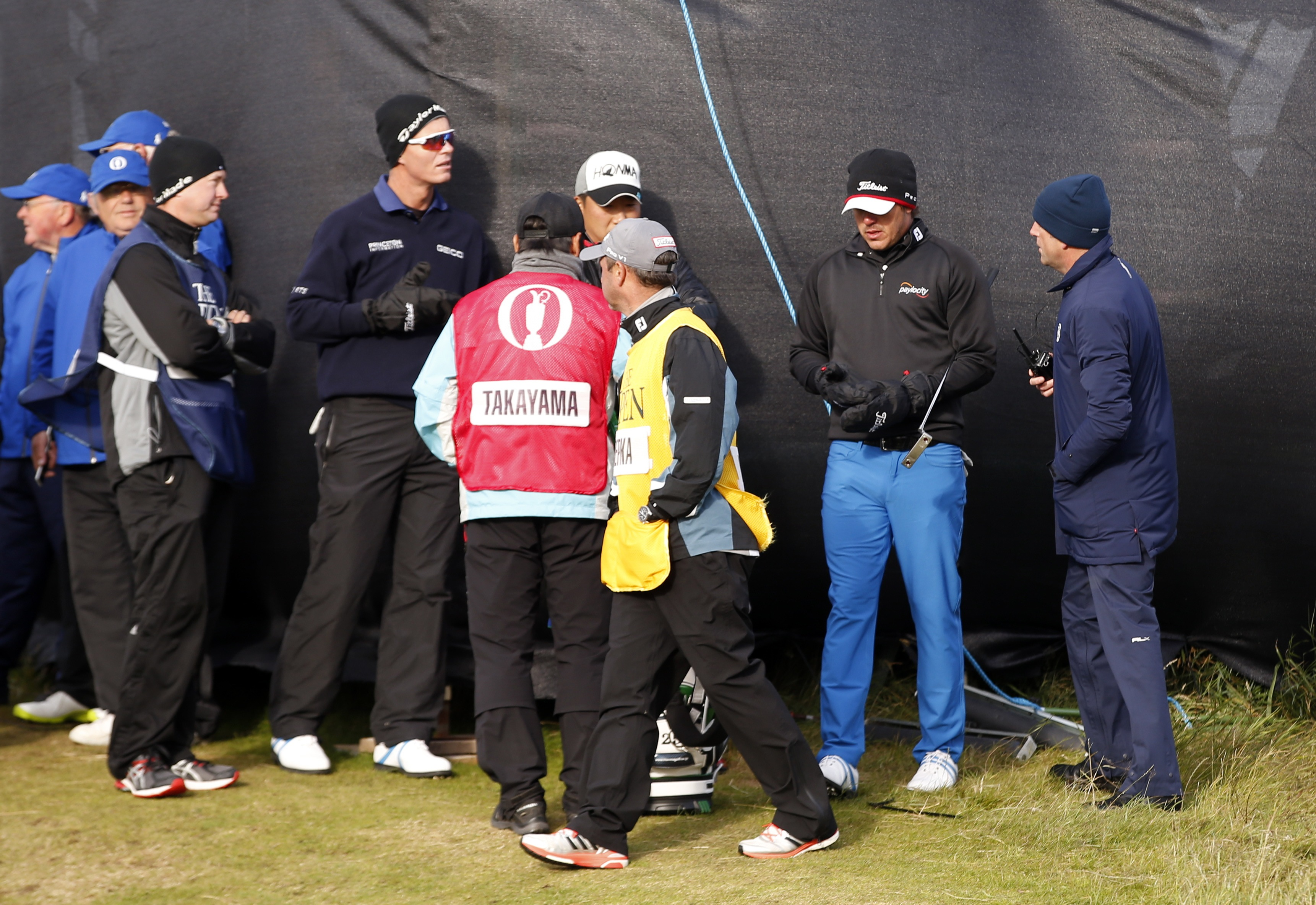 United States' Brooks Koepka, second from right, and others listen to an official as strong winds suspend play during the second round of the British Open Golf Championship at the Old Course, St. Andrews, Scotland, Saturday, July 18, 2015. Play was suspen