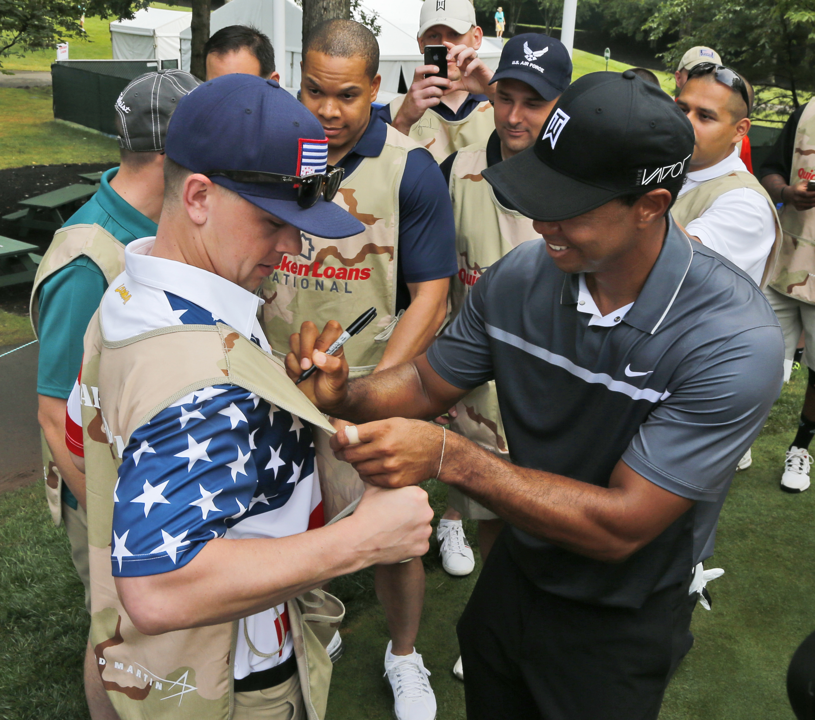 Tiger Woods autographs the vest of military caddie Coast Guard petty officer Chris Hopp, of Chicago, during the pro-am for the Quicken Loans National Golf tournament at the Robert Trent Jones Golf Club in Gainesville, Va., Wednesday, July 29, 2015.  (AP P