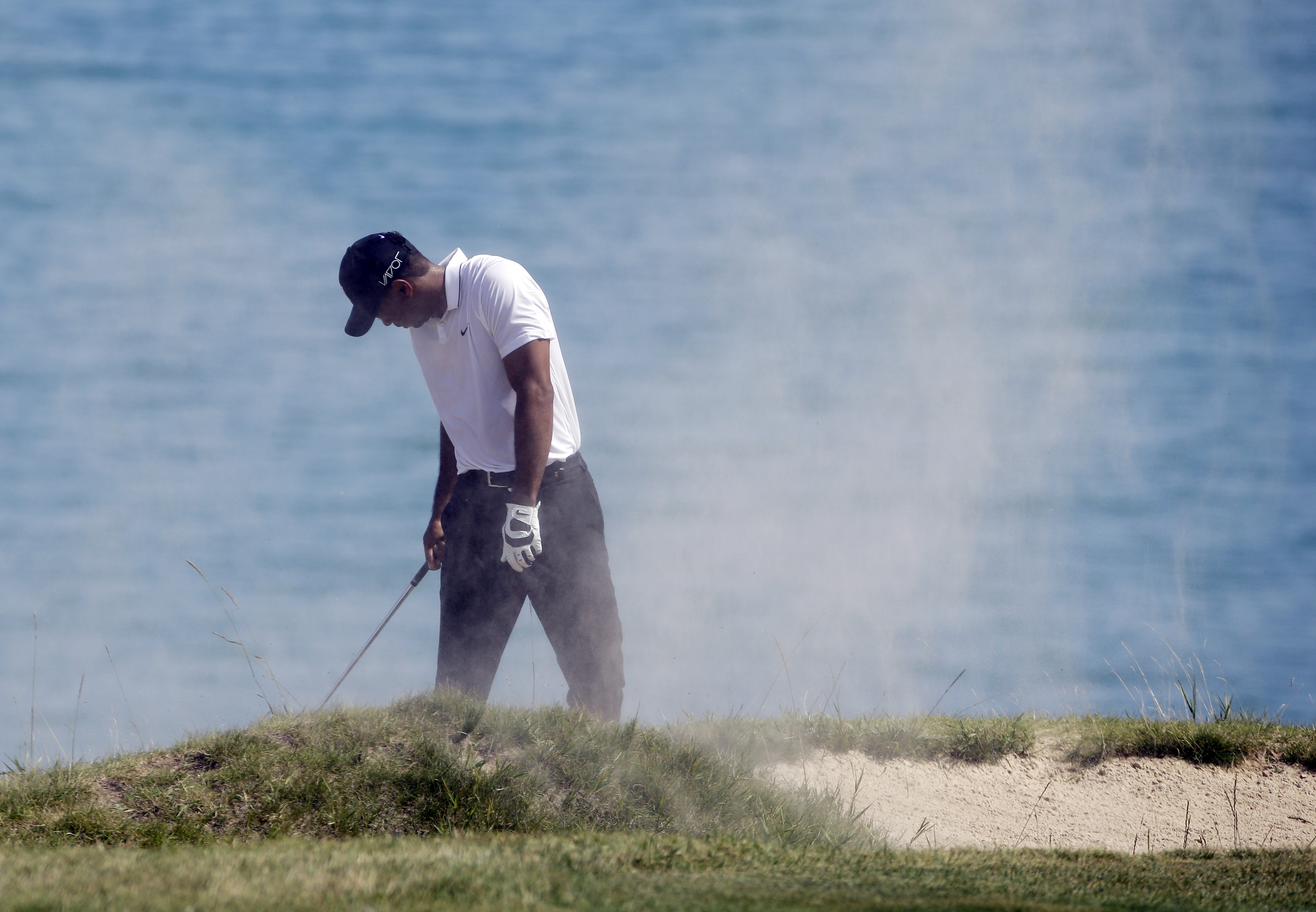 Tiger Woods covers his face after hitting from a bunker on the fourth holeduring the second round of the PGA Championship golf tournament Friday, Aug. 14, 2015, at Whistling Straits in Haven, Wis. (AP Photo/Brynn Anderson)