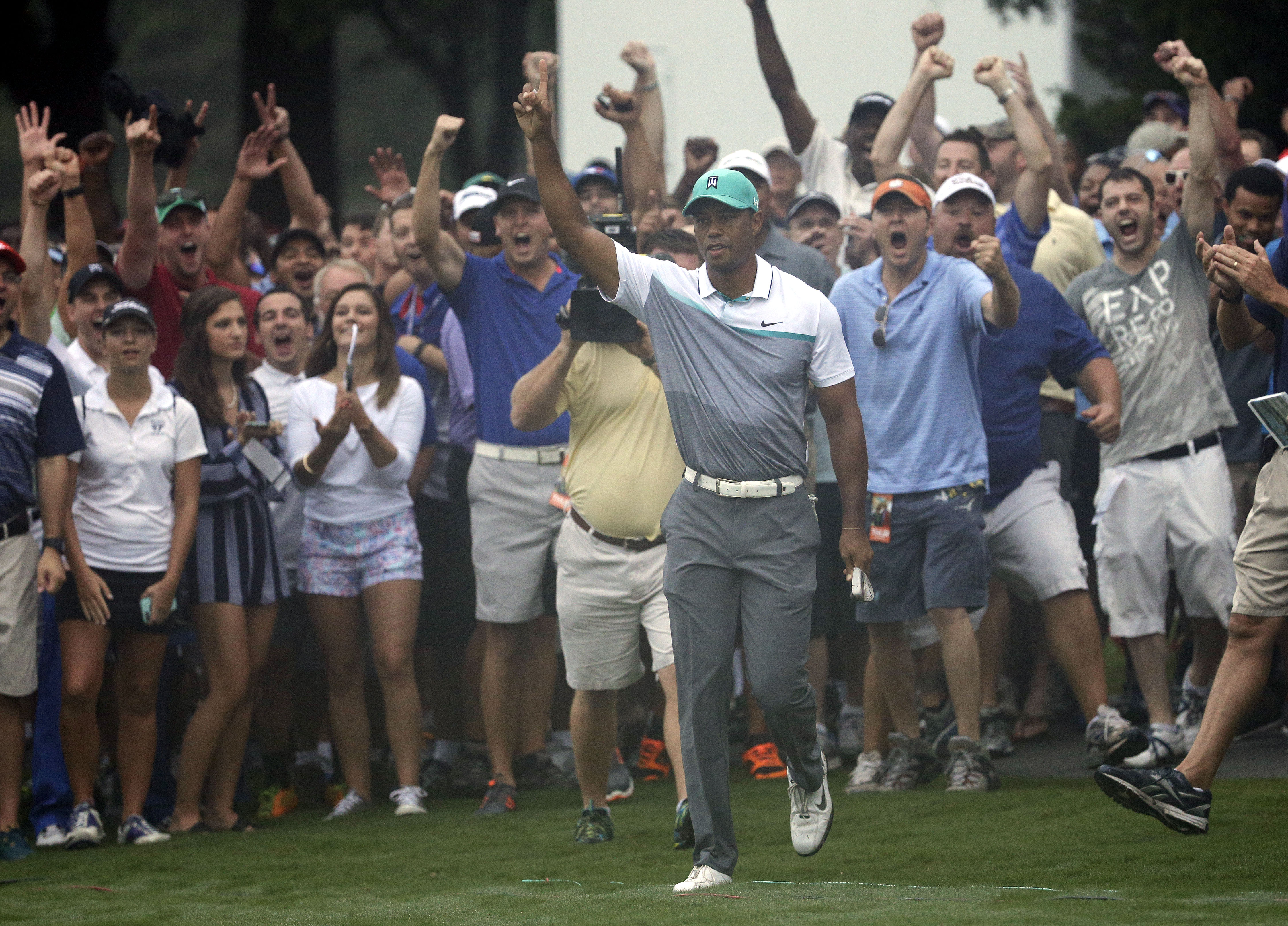 Tiger Woods reacts after holing out a chip shot on the 10th hole during the first round of the Wyndham Championship golf tournament in Greensboro, N.C., Thursday, Aug. 20, 2015. (AP Photo/Chuck Burton)