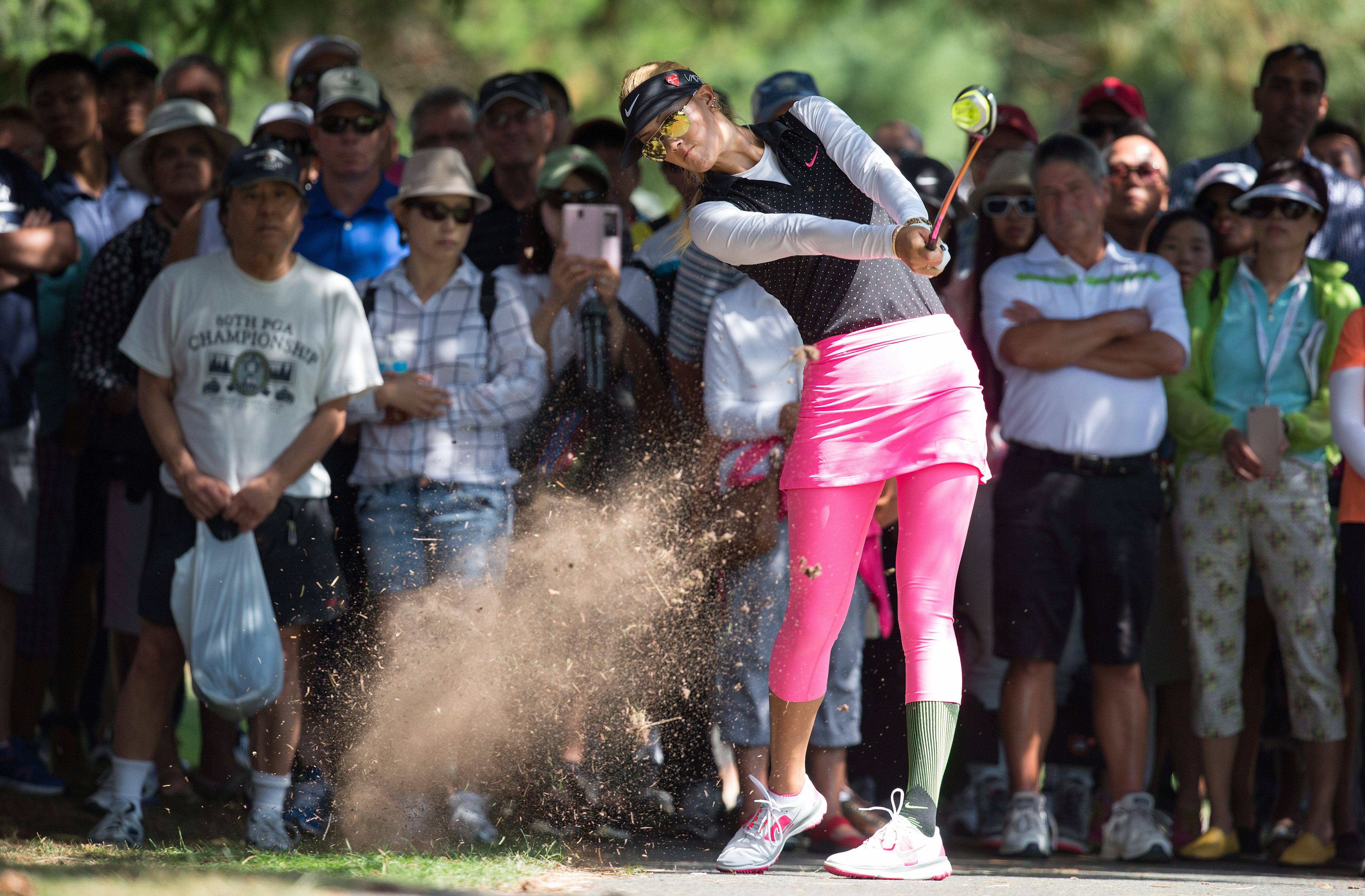 Michelle Wie, of the United States, hits her second shot out of the rough beside a cart path on the sixth hole during the second round of the Canadian Open golf tournament at the Vancouver Golf Club in Coquitlam, British Columbia, Friday, Aug. 21, 2015. (