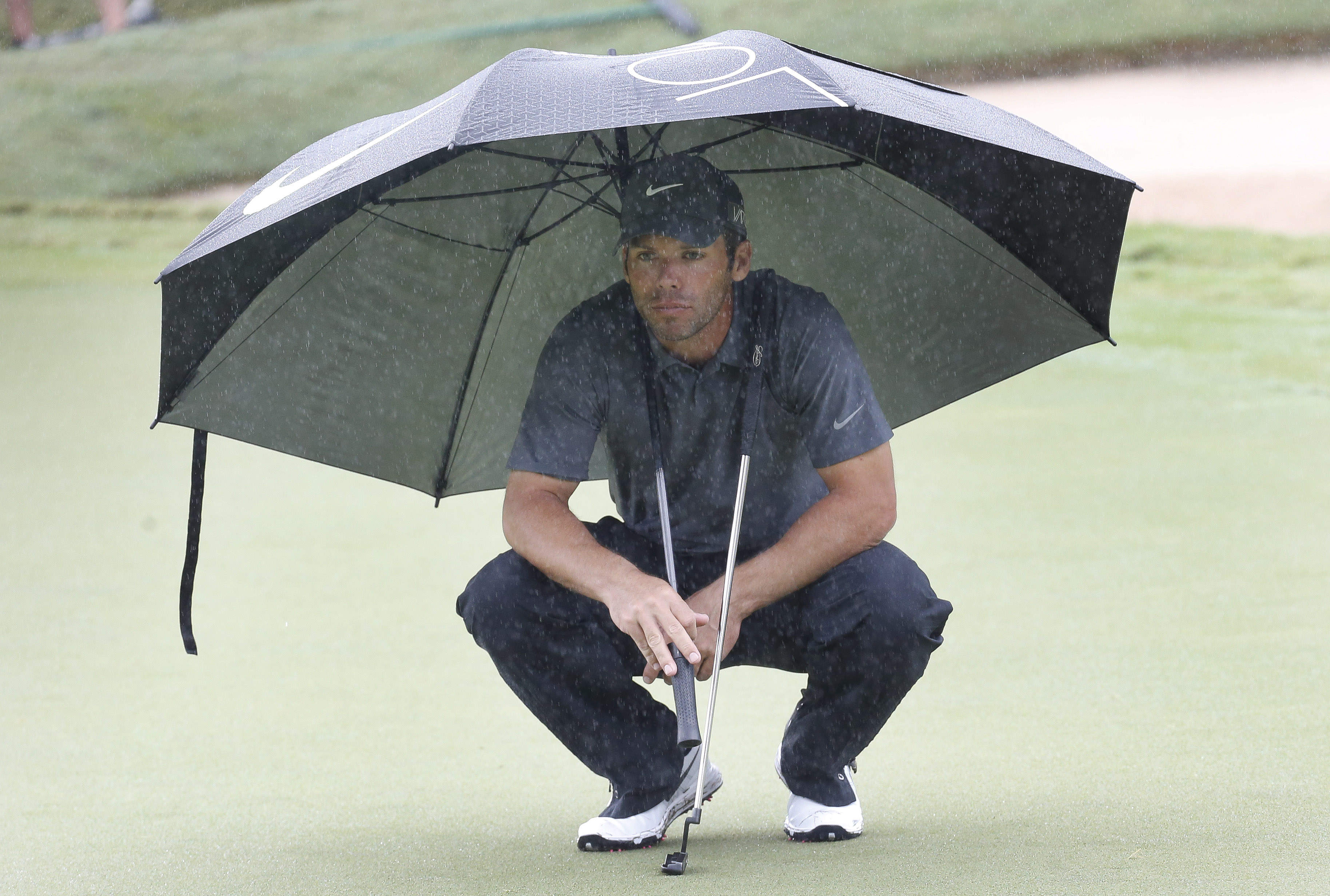 Paul Casey takes cover under an umbrella as he waits to putt on the third hole during the second round of the Tour Championship golf tournament at East Lake Club Friday, Sept. 25, 2015, in Atlanta. (AP Photo/ John Bazemore)