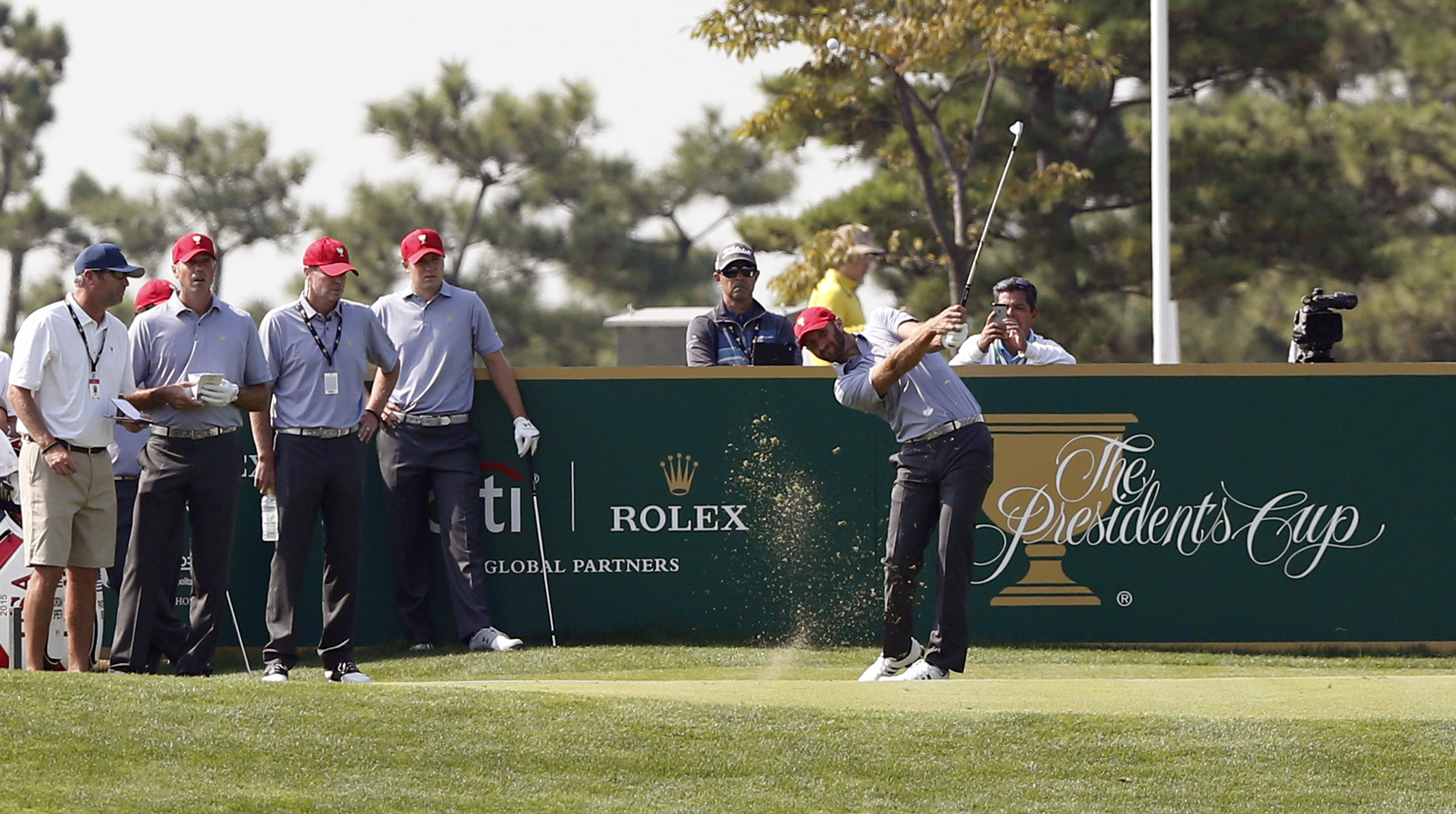 United States team player Dustin Johnson tees off as team captain's assistant Steve Stricker, third from left, and team players Matt Kuchar, second from left and Jordan Spieth watch during a practice round ahead of the Presidents Cup golf tournament at Ja
