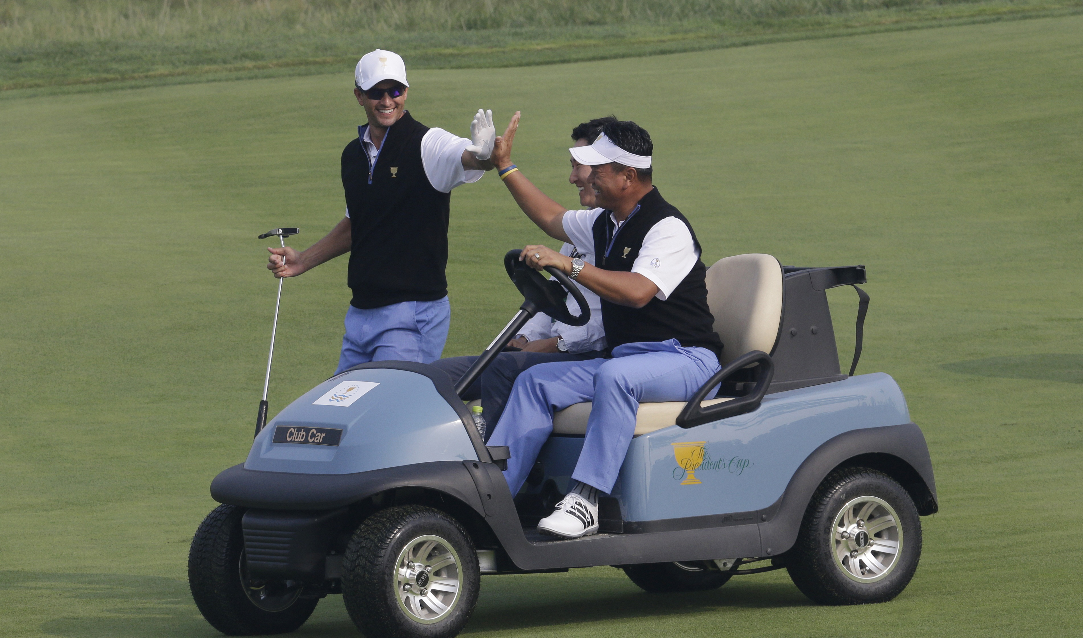 International team player Adam Scott, left, gives a high-five to his team vice-captain K.J. Choi on the 11th hole during a practice round ahead of the Presidents Cup golf tournament at Jack Nicklaus Golf Club Korea in Incheon, South Korea, Wednesday, Oct.