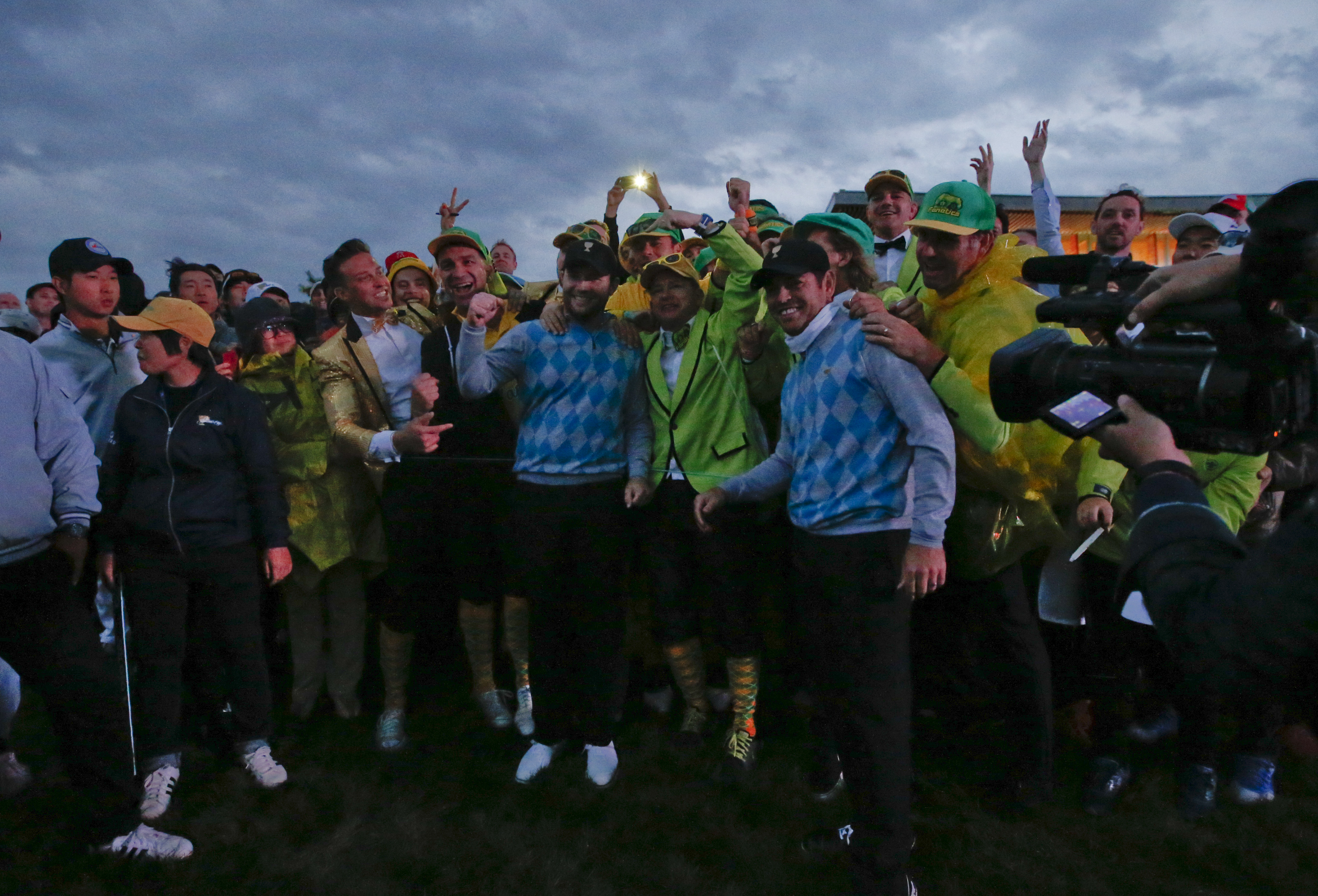 International team player's Branden Grace of South Africa and compatriot Louis Oosthuizen are surrounded by fans after they won their four ball match in fading light at the Presidents Cup golf tournament at the Jack Nicklaus Golf Club Korea, in Incheon, S