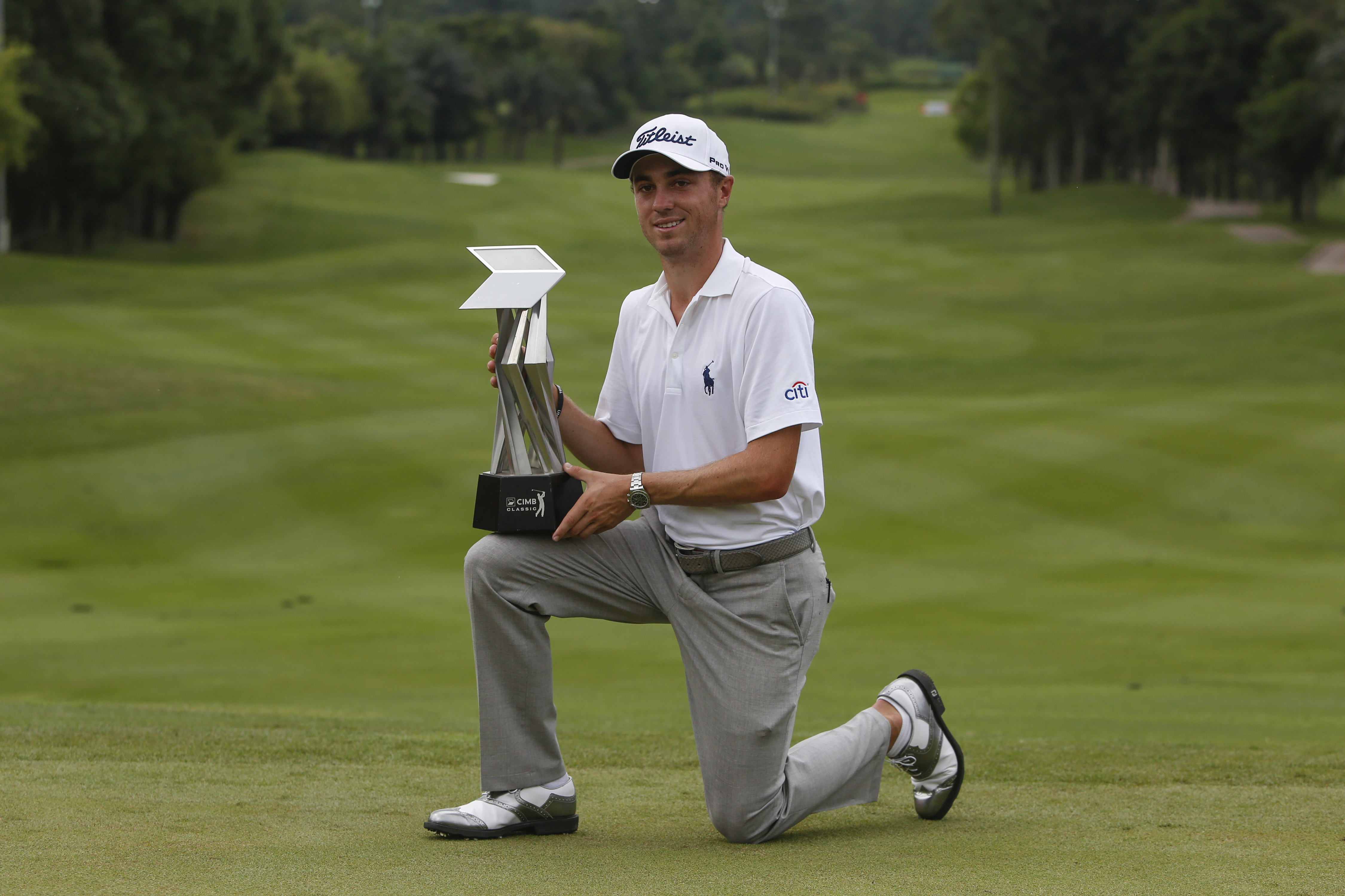Justin Thomas of the United States poses with his trophy after winning the CIMB Classic golf tournament at Kuala Lumpur Golf and Country Club in Kuala Lumpur, Malaysia, Sunday, Nov. 1, 2015. (AP Photo/Joshua Paul)