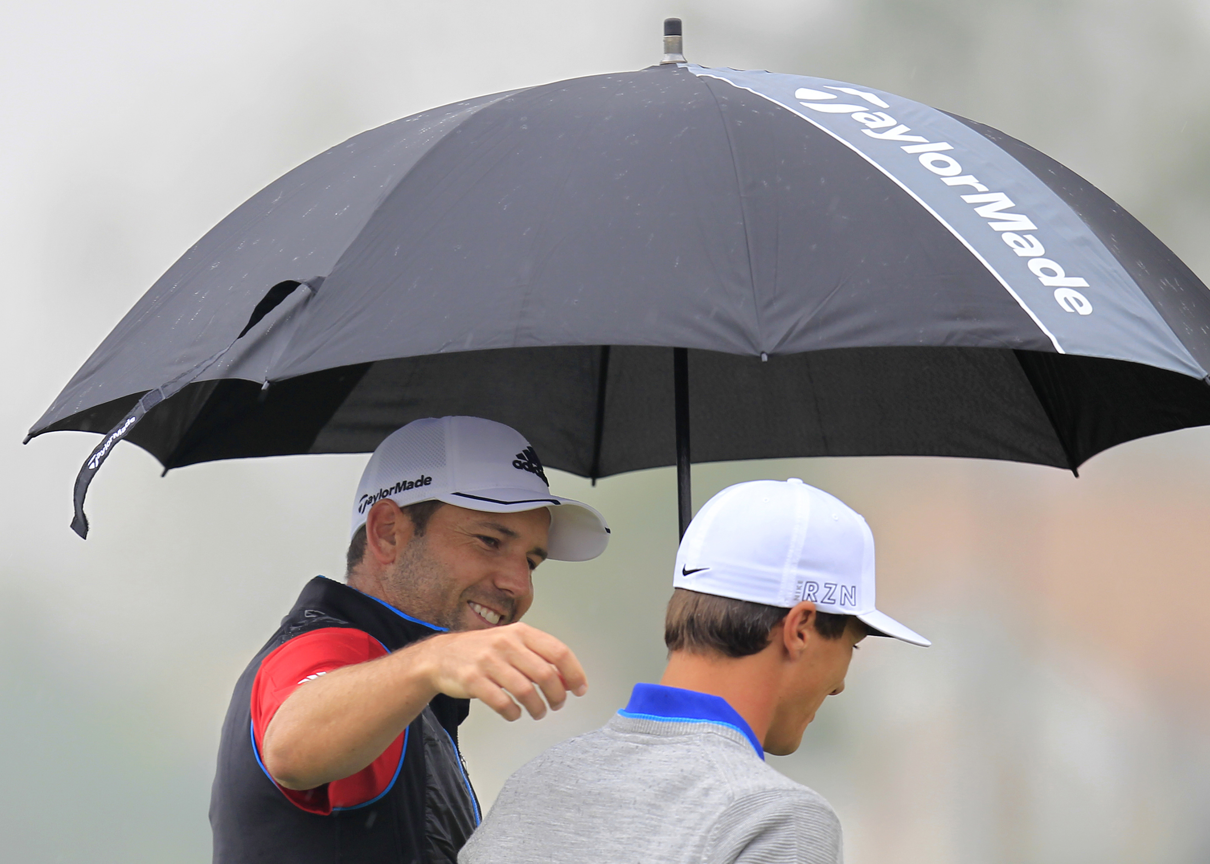 Sergio Garcia of Spain, left, gestures as he walks with Thorbjorn Olesen of Denmark, right, on the 15th hole during the first round of the BMW Masters golf tournament at the Lake Malaren Golf Club in Shanghai, China Thursday, Nov. 12, 2015. (AP Photo)