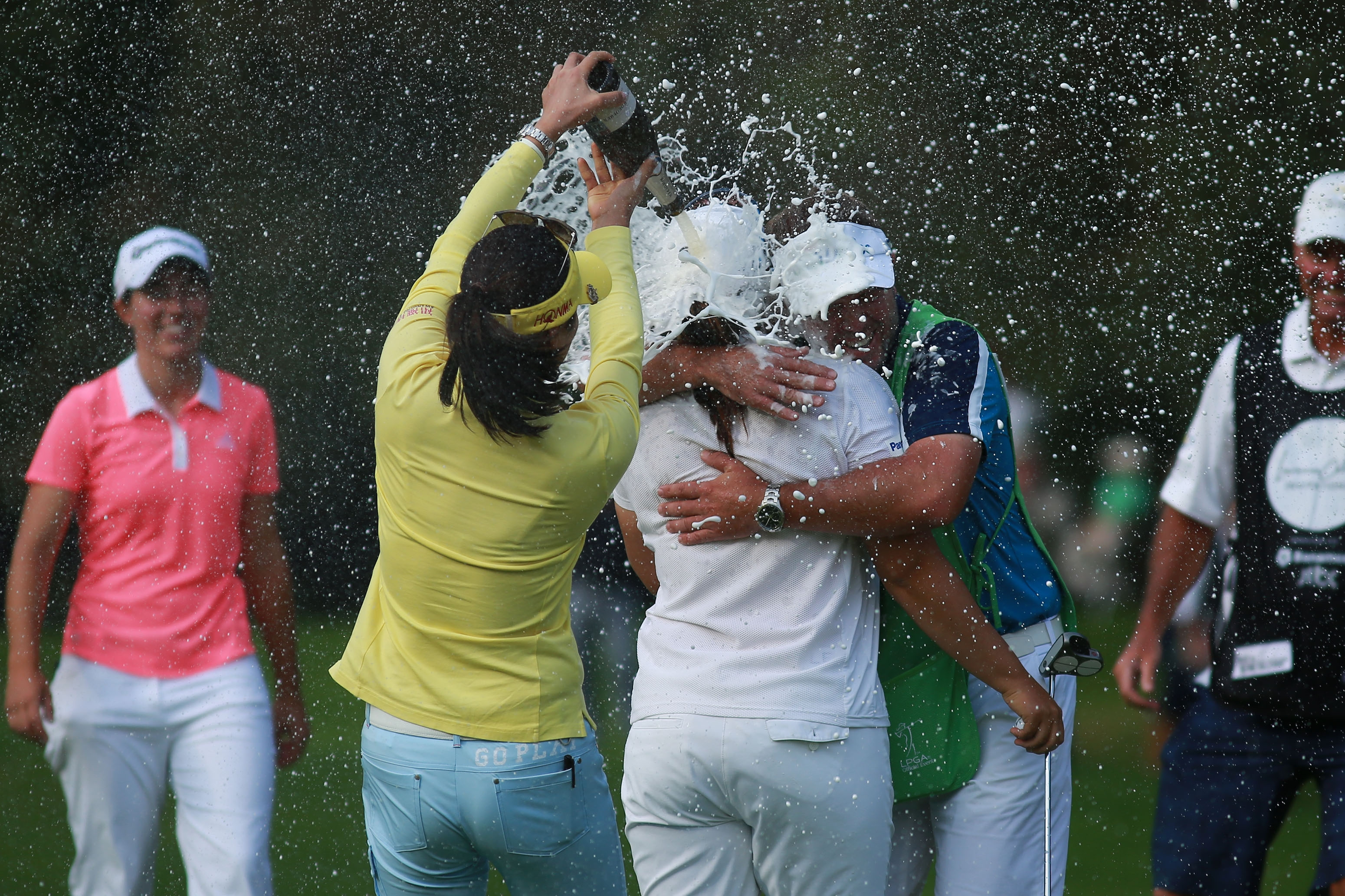 South Korea's So Yeon Ryu, second left, pours Champaign as South Korea's Inbee Park embraces with caddy Brad Beecher after winning the LPGA Lorena Ochoa Invitational in Mexico City, Sunday, Nov. 15, 2015. Inbee Park won the Invitational, holding off Carlo