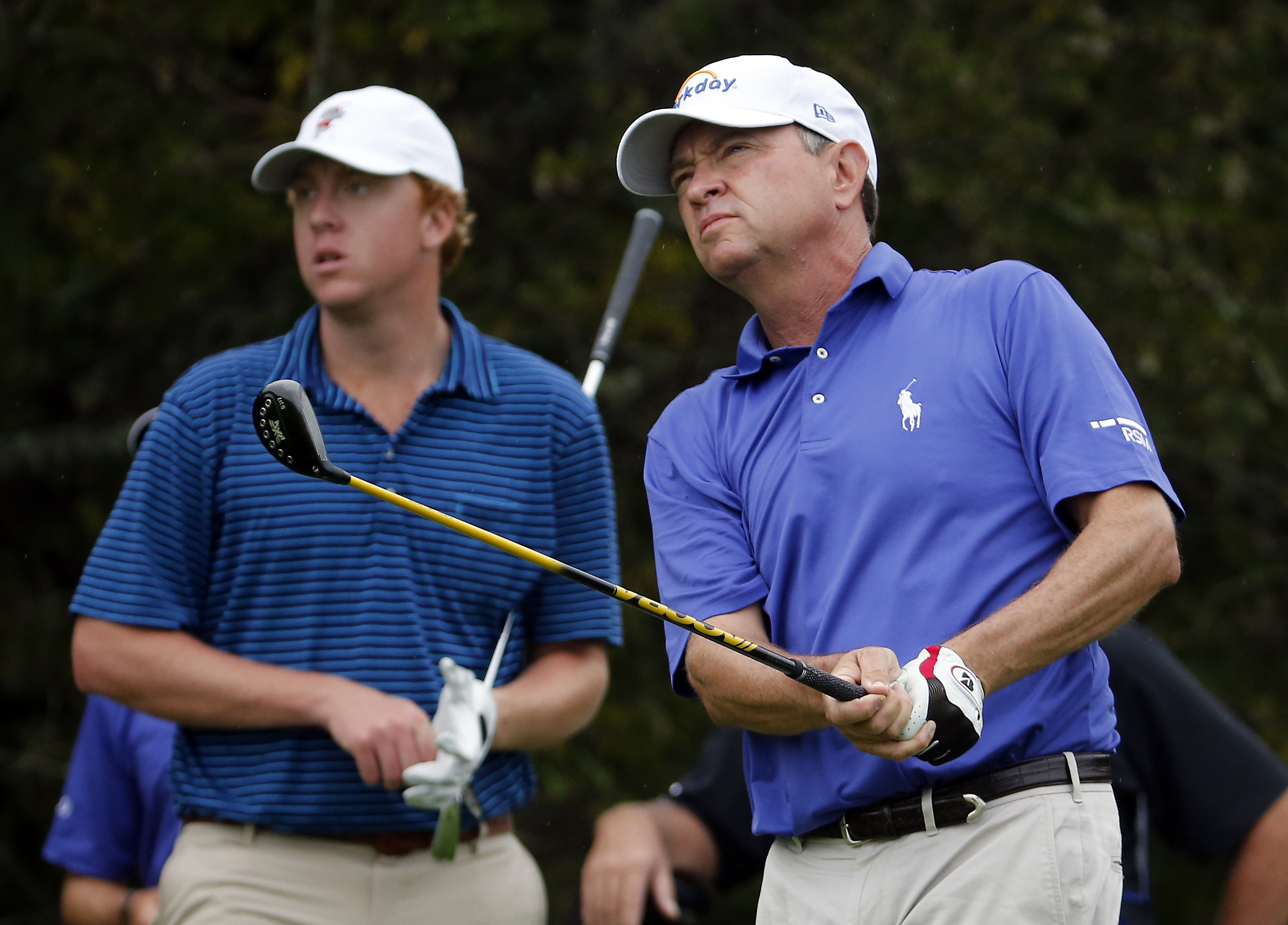 Davis Love III, right, watches his drive from the second tee, while his son Davis Love IV, left, looks on during the first round at the RSM Classic golf tournament, Thursday, Nov 19, 2015, in St. Simons Island, Ga. (AP Photo/Stephen B. Morton)