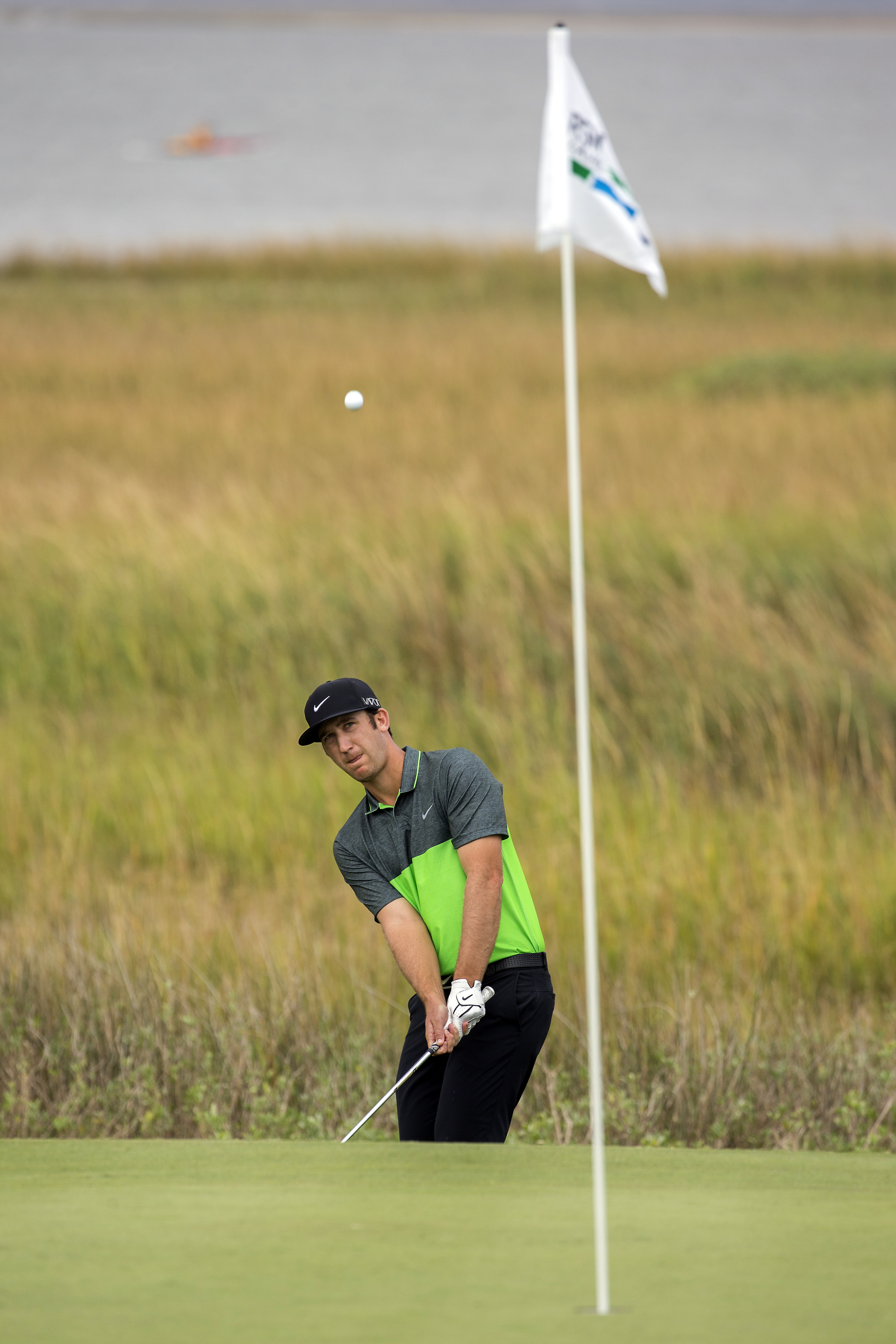 Kevin Chappell watches his chip shot onto the 14th green on the Seaside Course at Sea Island Golf Club during the third round at the RSM Classic golf tournament, Saturday, Nov. 21, 2015, in St. Simons Island, Ga. (AP Photo/Stephen B. Morton)