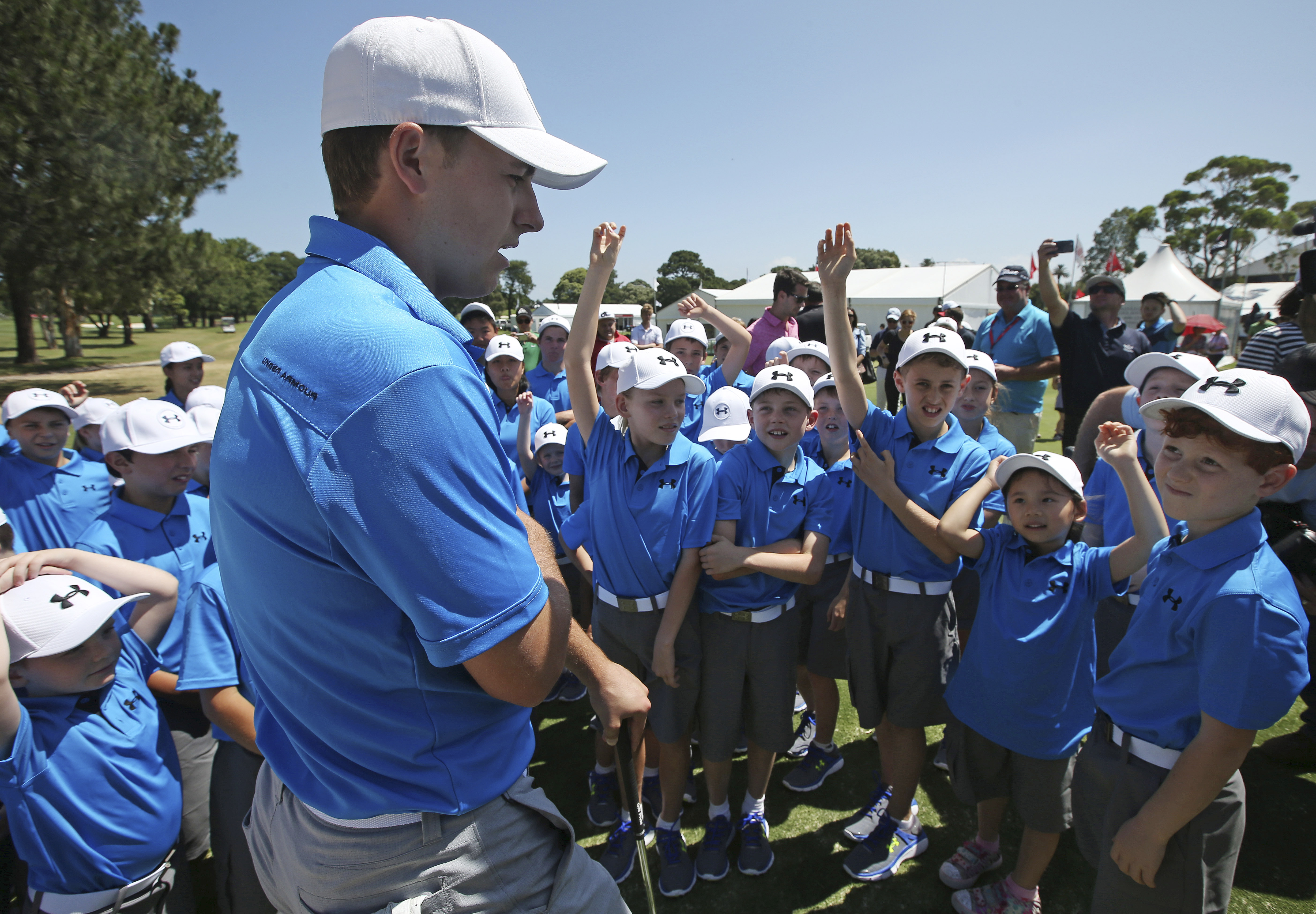 American golfer Jordan Spieth, center, answers a few questions as he runs a clinic for young golfers at the Australian Golf Club in Sydney, Tuesday, Nov. 24, 2015. Spieth will defend his Australian Open title starting Thursday. (AP Photo/Rick Rycroft)