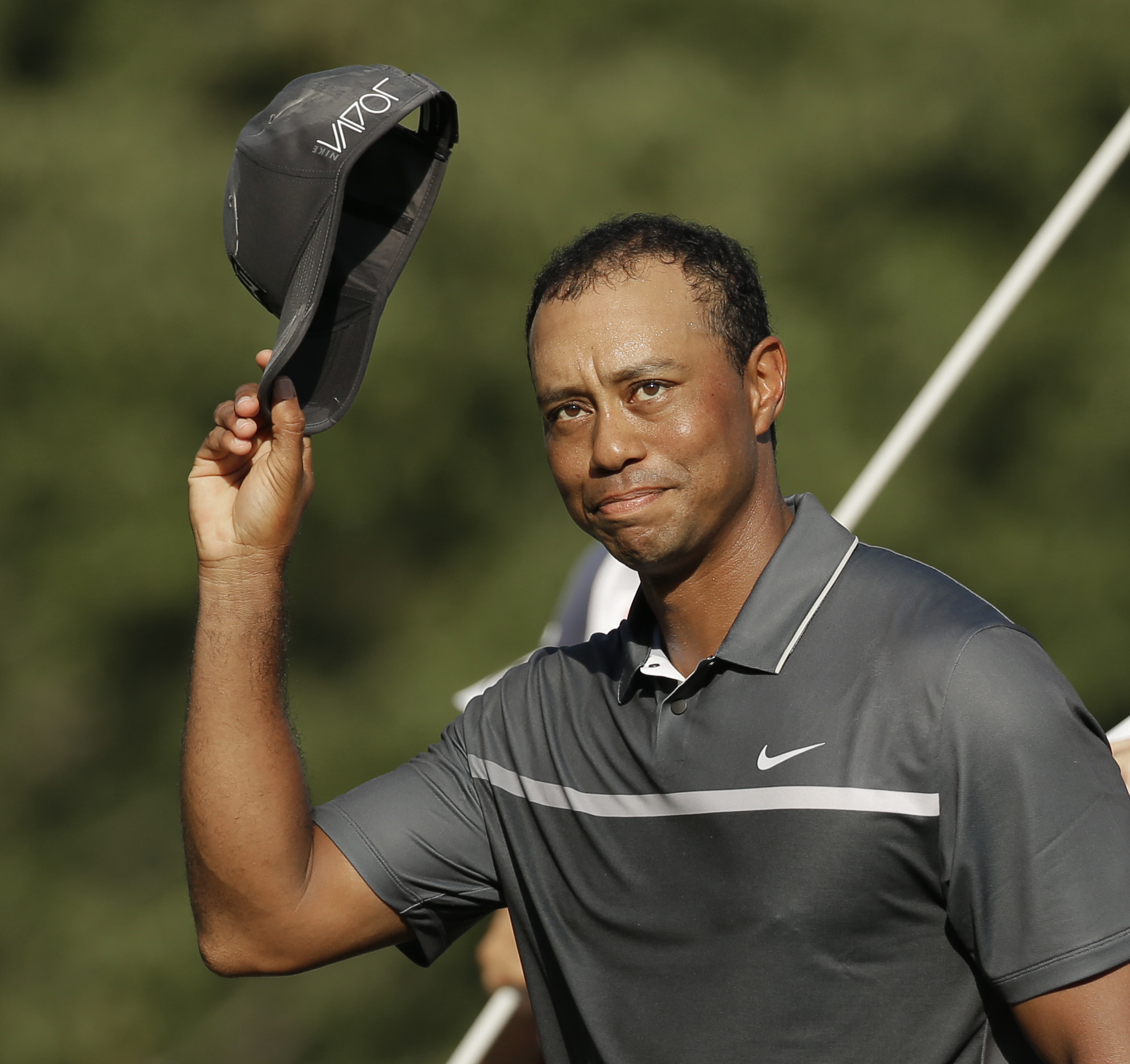 FILE - In this Aug. 21, 2015, file photo, Tiger Woods tips his hat to the crowd after finishing his round on the 18th hole during the second round of the Wyndham Championship golf tournament in Greensboro, N.C. Tiger Woods painted a bleak picture Tuesday,