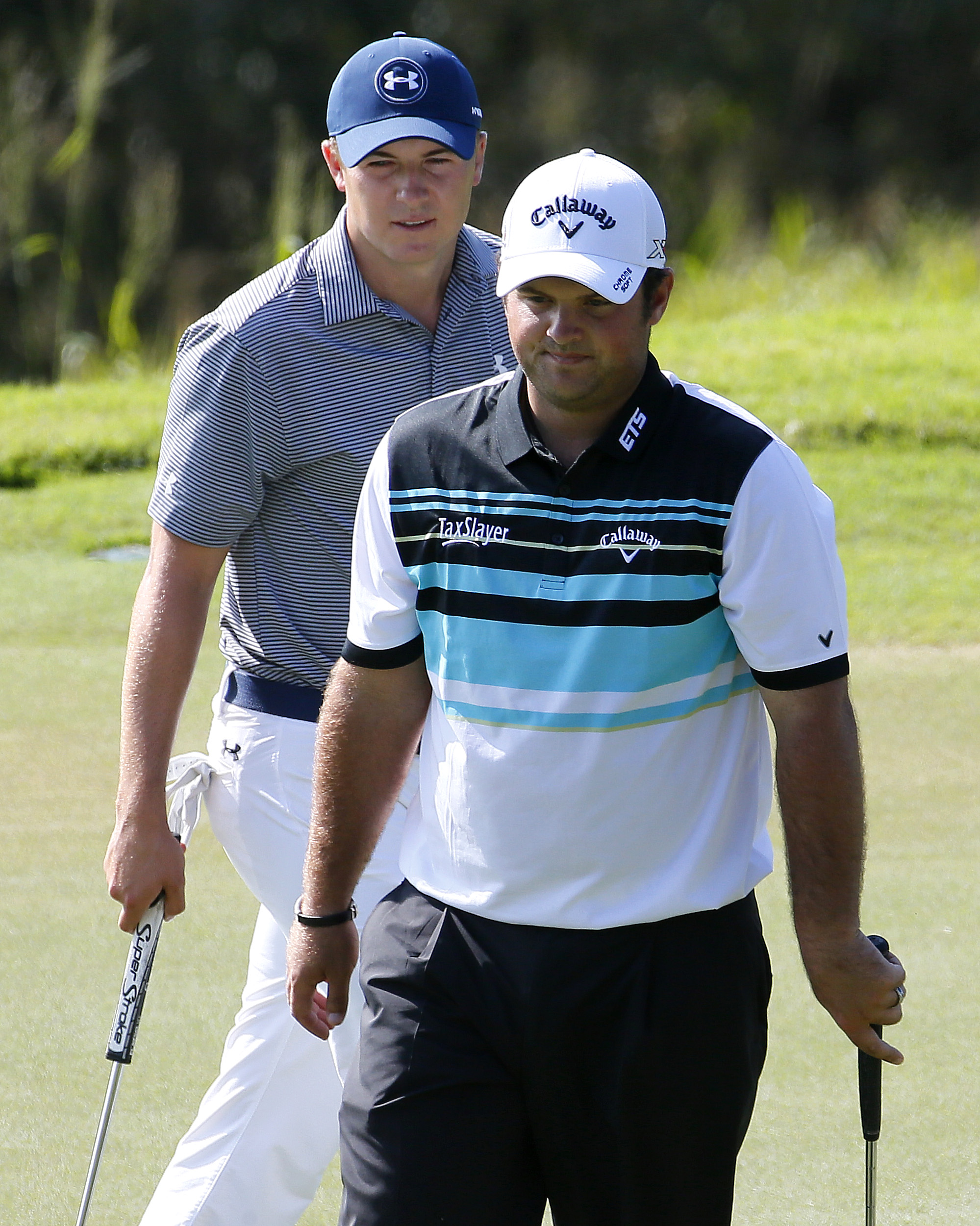 Jordan Spieth, rear, and Patrick Reed walks to their golf balls on the eighth green during the second round of the Tournament of Champions on Friday, Jan. 8, 2016, in Kapalua Plantation Course on Kapalua, Hawaii. (AP Photo/Matt York)