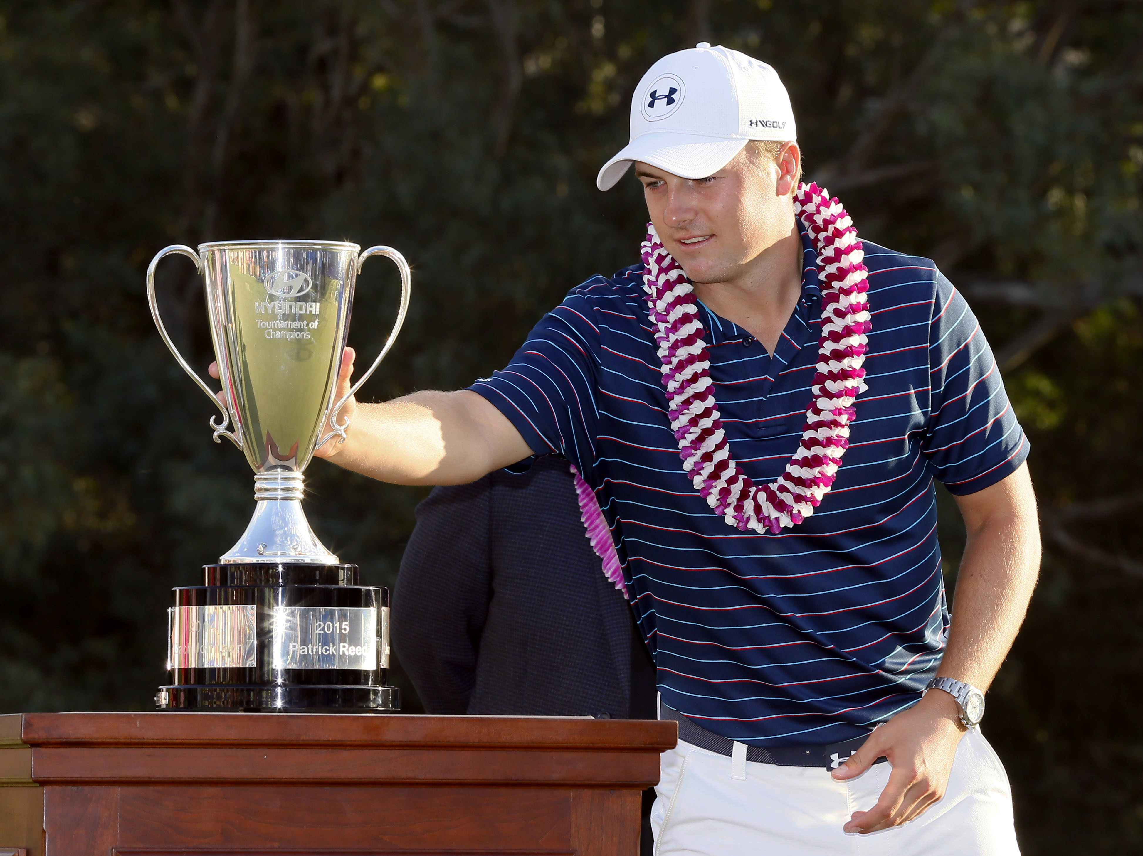 Jordan Spieth places the trophy on the podium after the final round of the Tournament of Champions golf event, Sunday, Jan. 10, 2016, at Kapalua Plantation Course in Kapalua, Hawaii. Spieth finished at 30 under par for the tournament win. (AP Photo/Matt Y