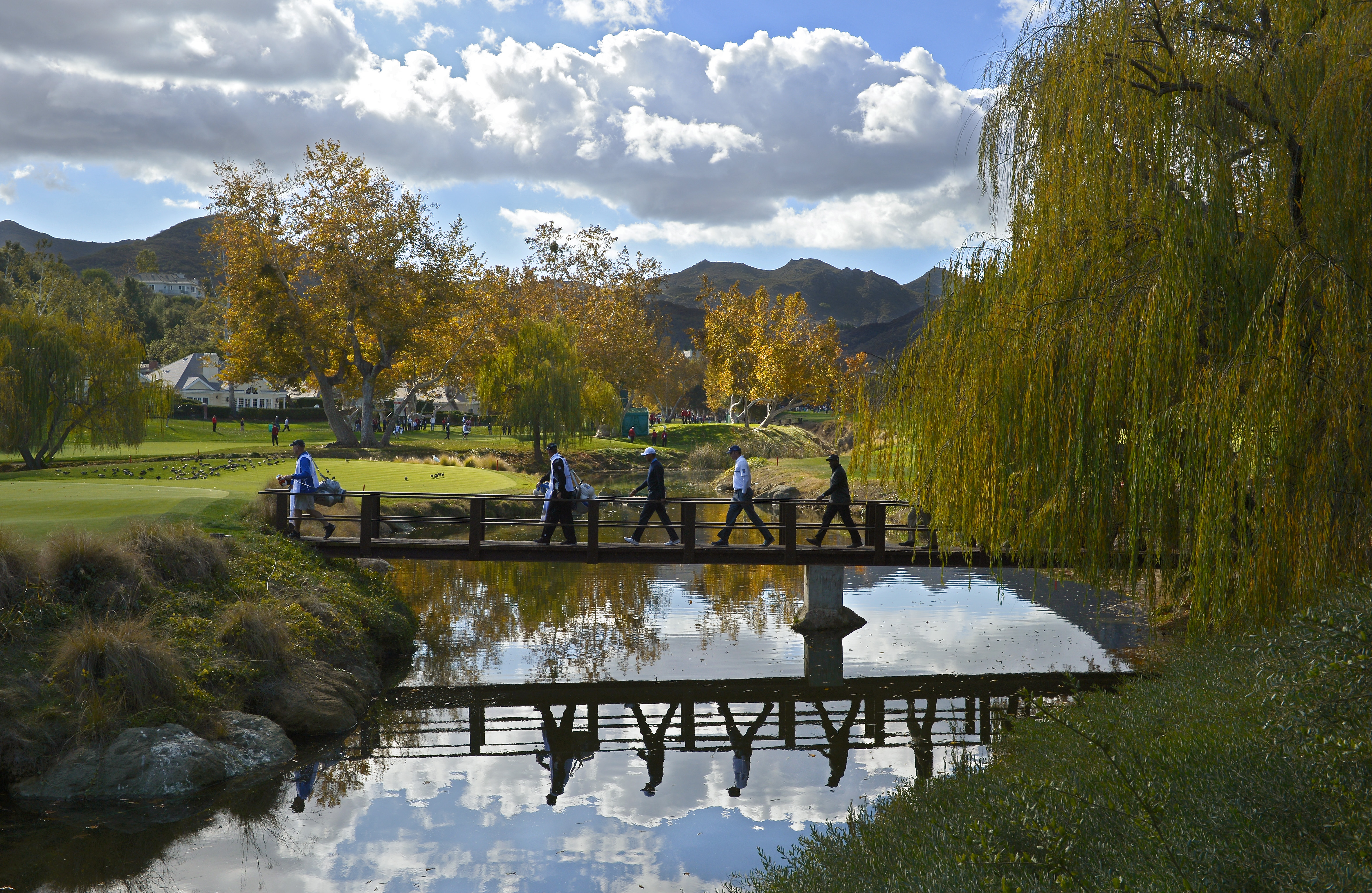 The group of Tiger Woods and Matt Kuchar walk across a bridge to get to the green on the second hole during the first round of the Northwestern Mutual World Challenge golf tournament at Sherwood Country Club, Thursday, Dec. 5, 2013, in Thousand Oaks, Cali